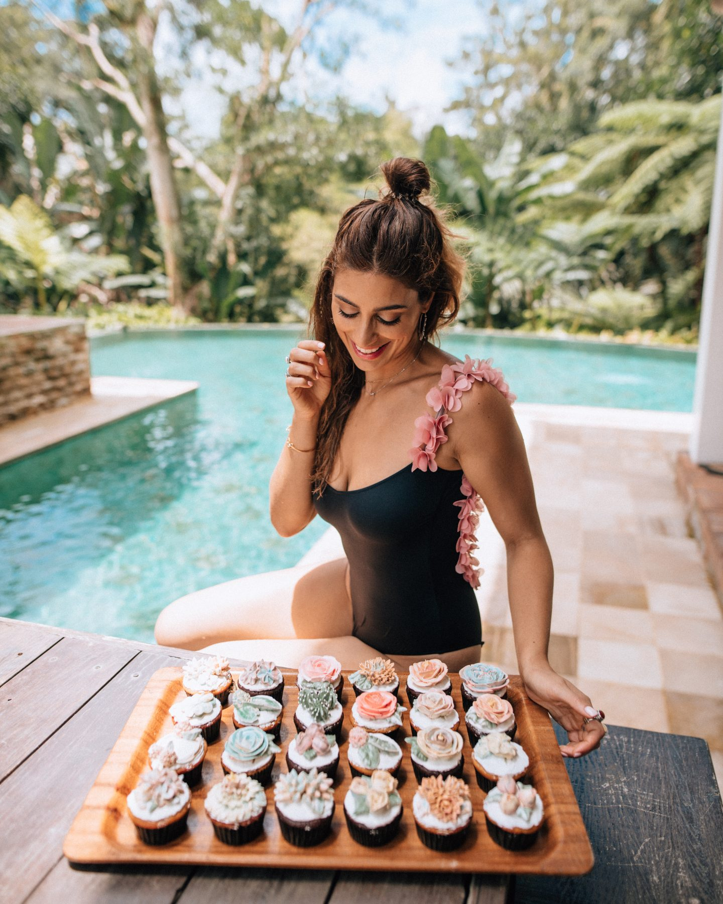 Woman looking at cupcakes near a pool at a villa in Bali
