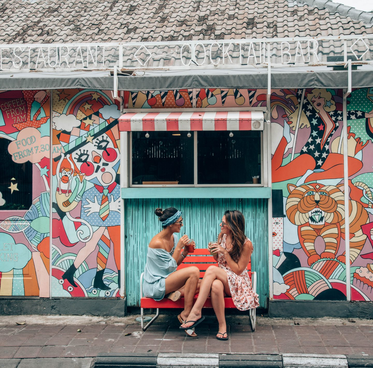 Two women sit outside of Sea Circus in Bali