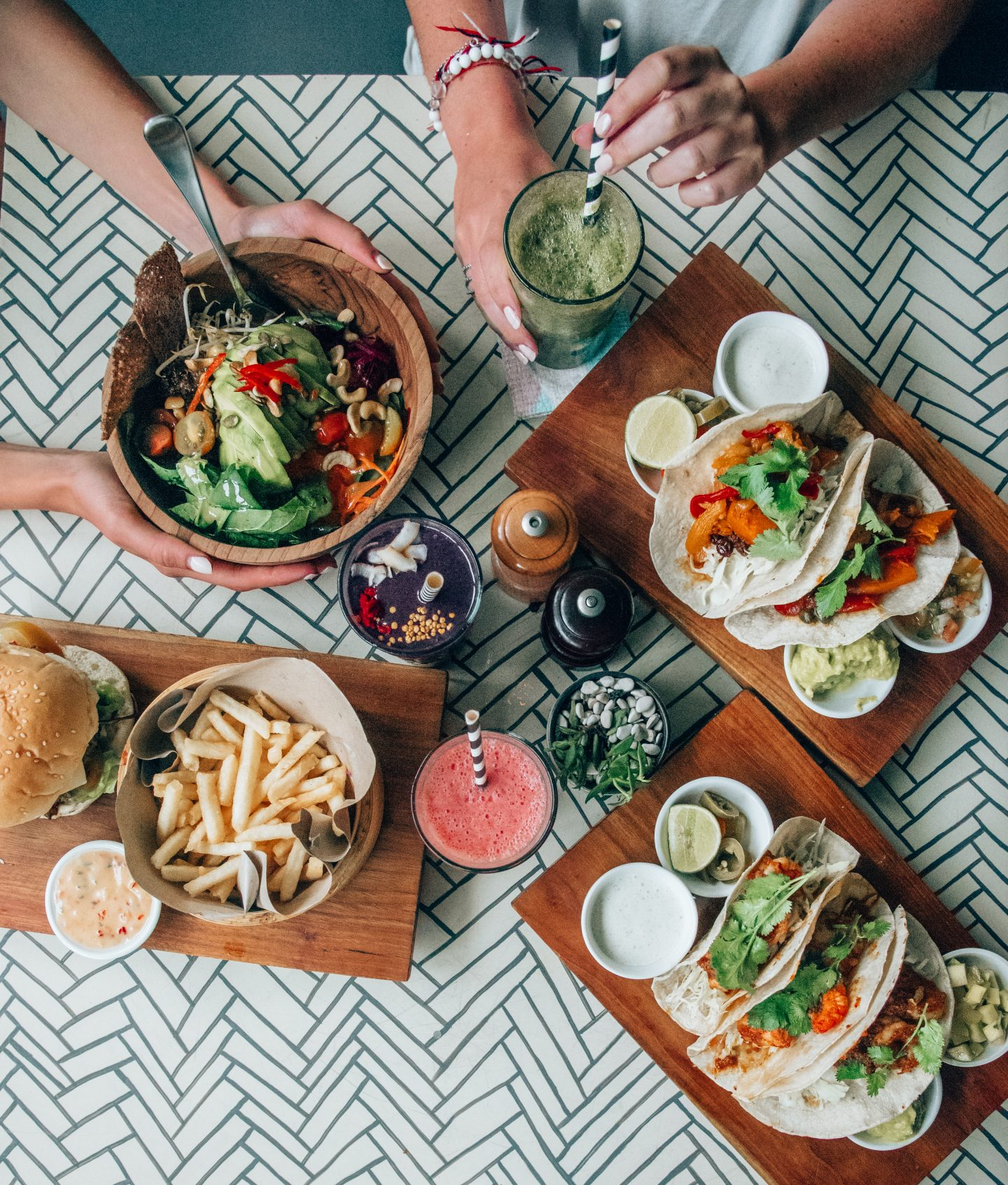 A flatlay of food from a cafe in Bali with salad, tacos, smoothies, and fries.