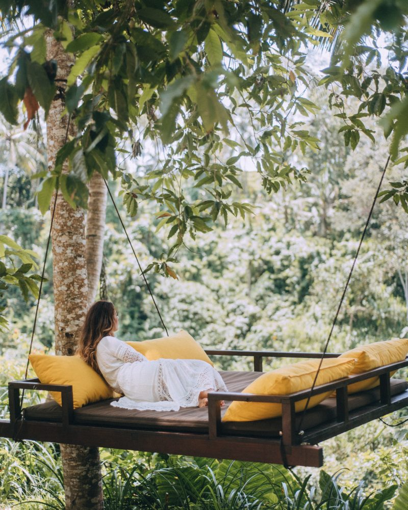 Woman in a swing in Bali that is also a day bed