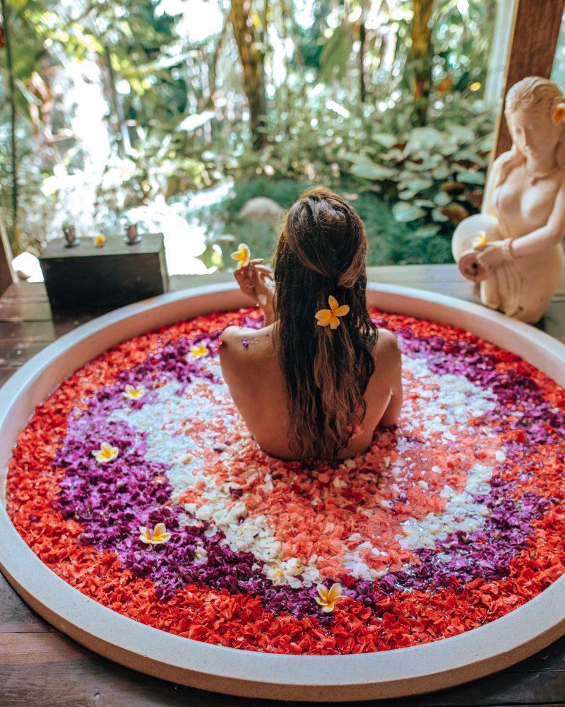 A woman in a flower bath at the Udaya in Ubud, Bali