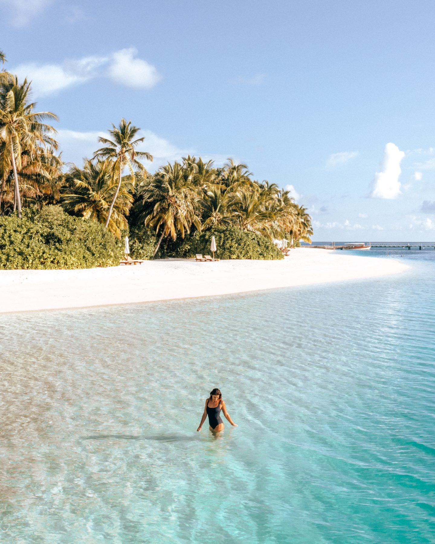 A woman in the water by the beach at Conrad Rangali Island in the Maldives