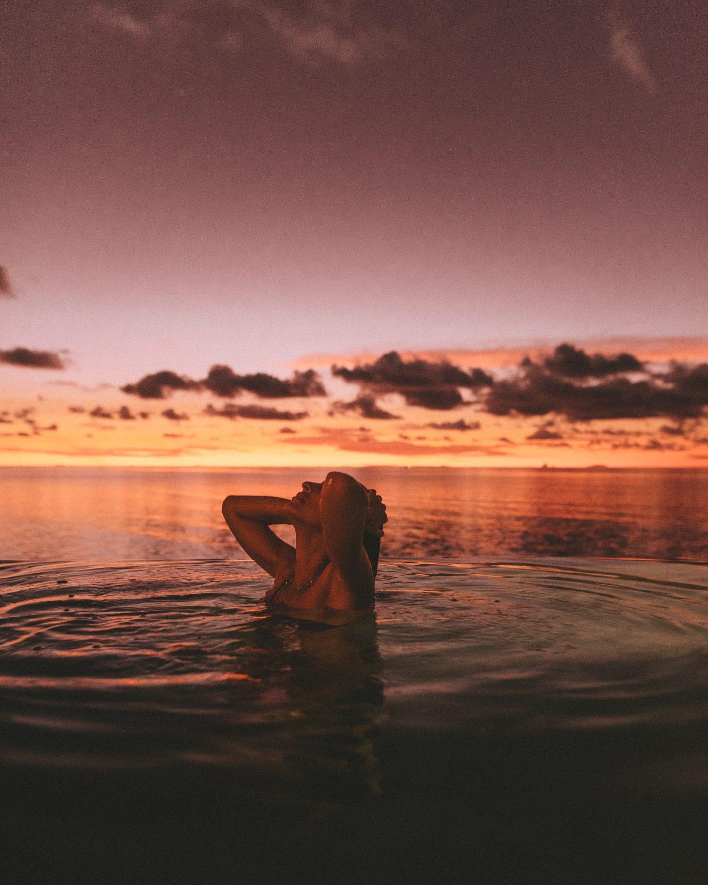 Woman in the pool at sunset at Anantara Dhigu