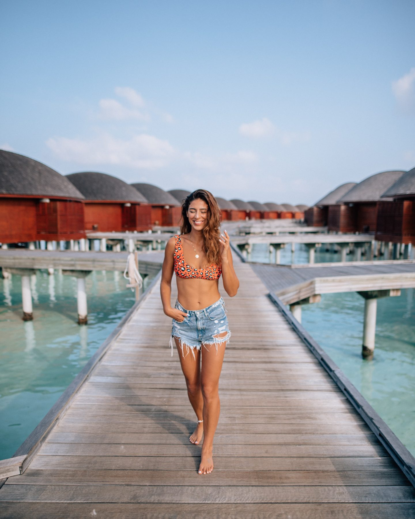 Woman on the walkway to the overwater bungalows at Anantara Dhigu in the Maldives
