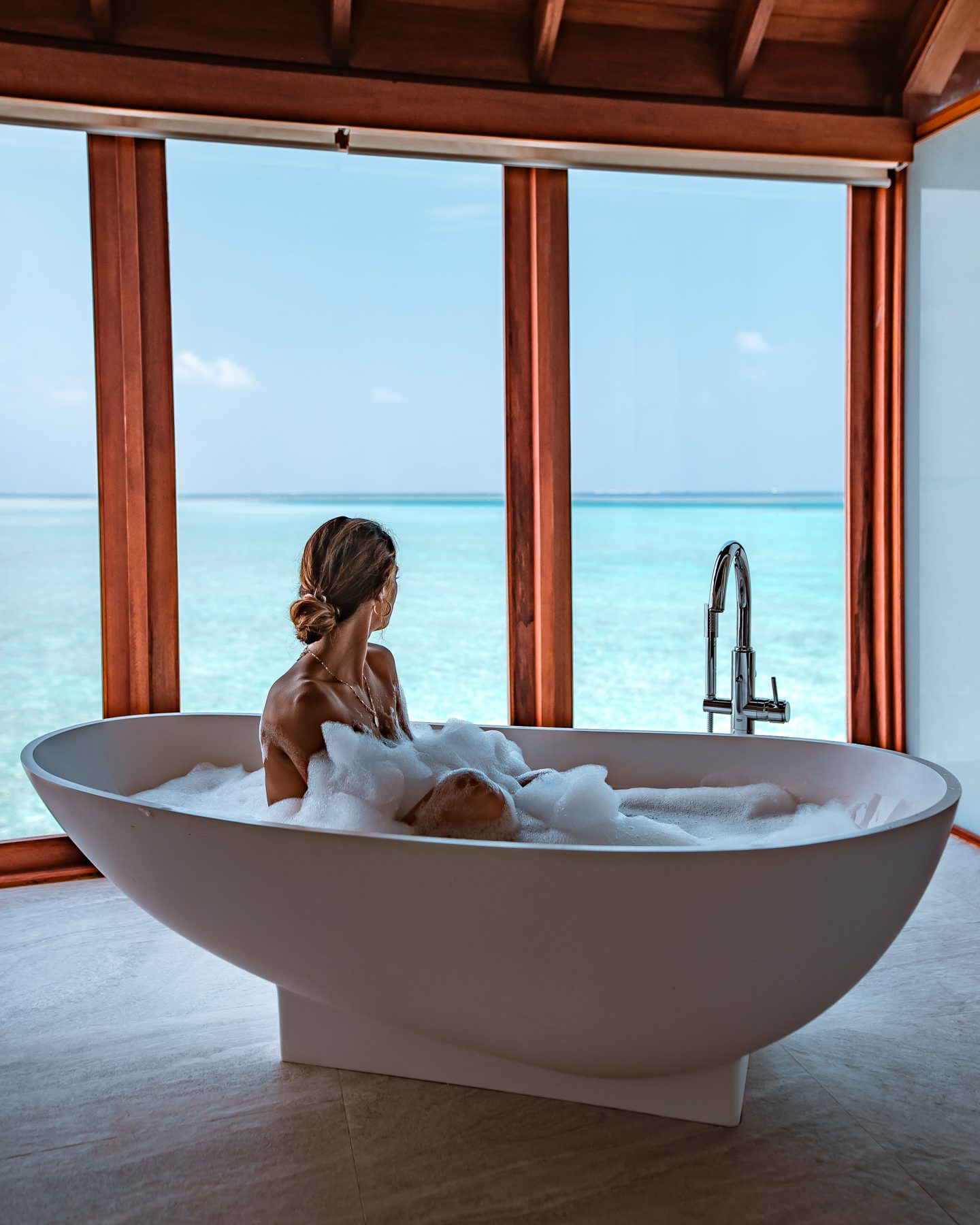 Woman in bathtub at Anantara Dhigu in the Maldives with an amazing view