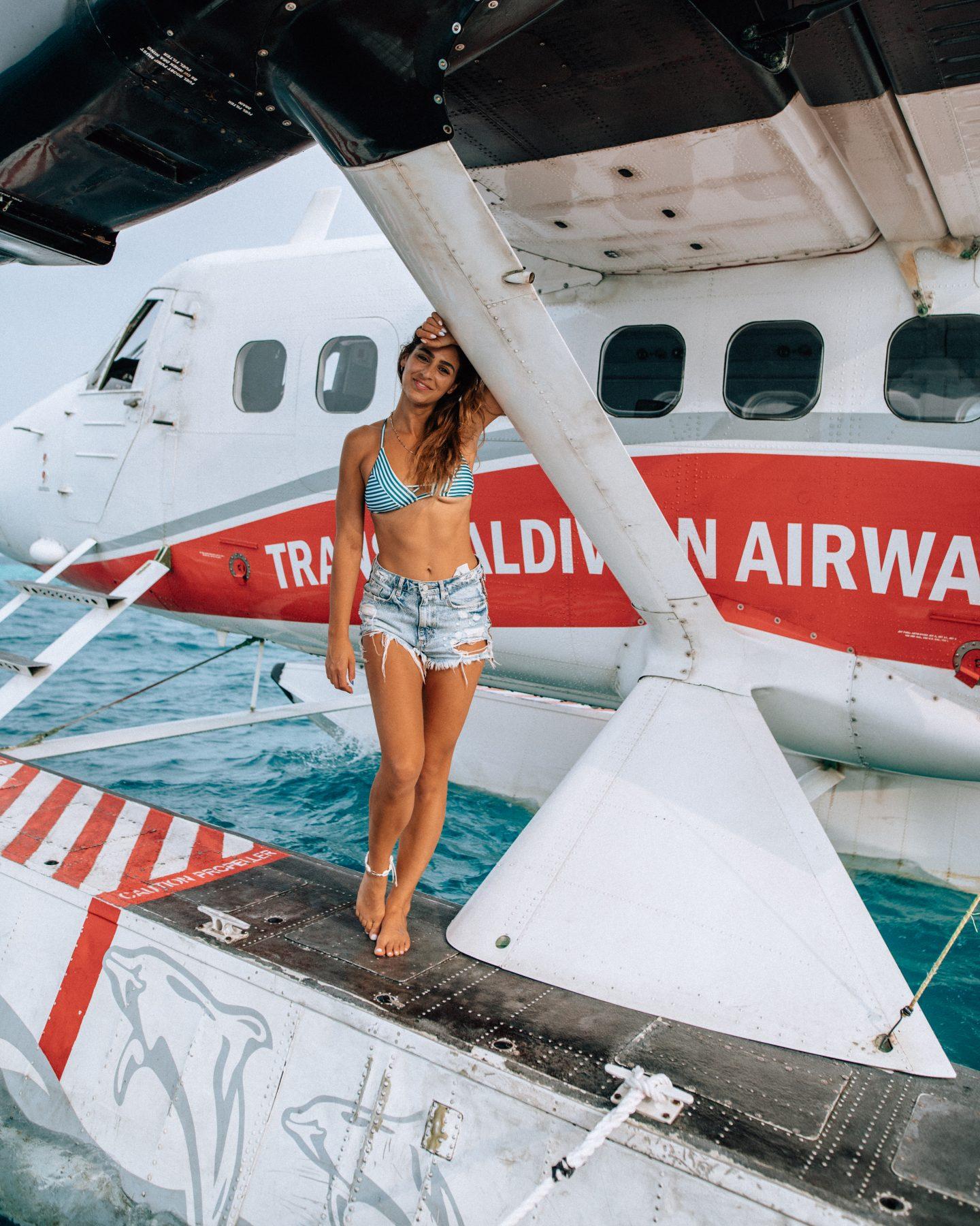 Woman in front of Trans Maldivian Seaplane in the Maldives