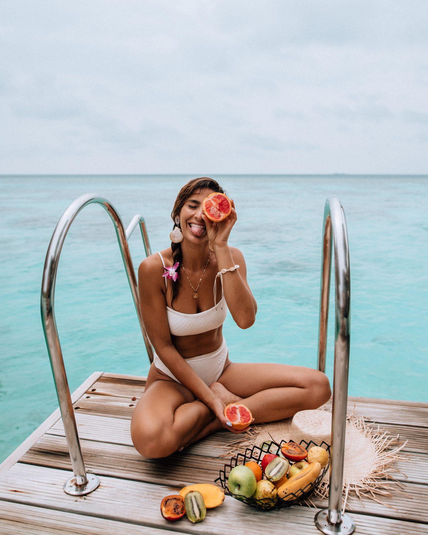 Woman eating on the dock at Kandolhu Maldives
