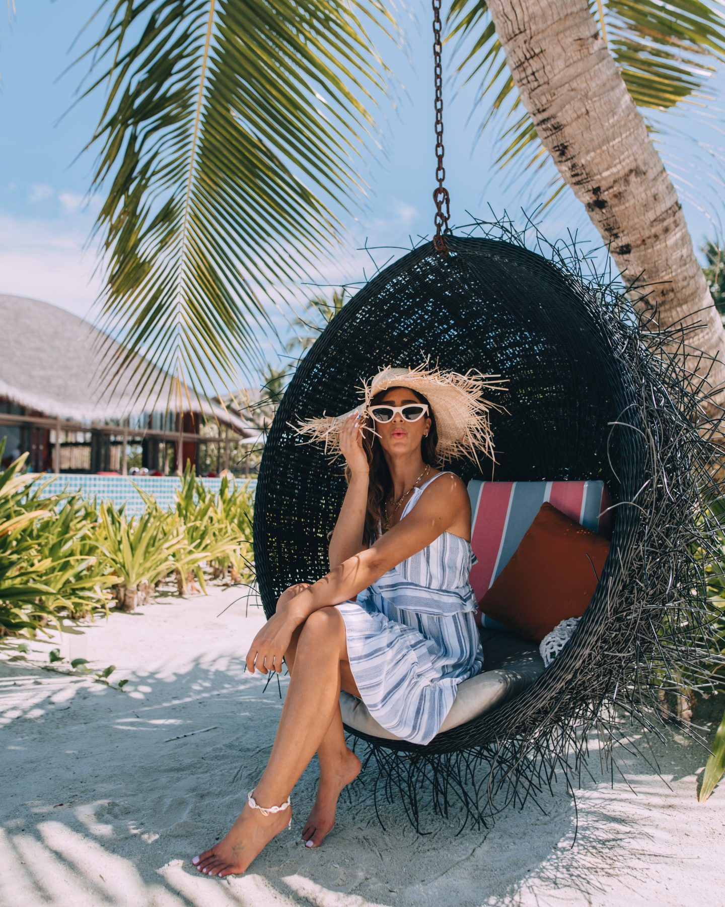 A woman relaxes on the beach at Club Med Finolhu