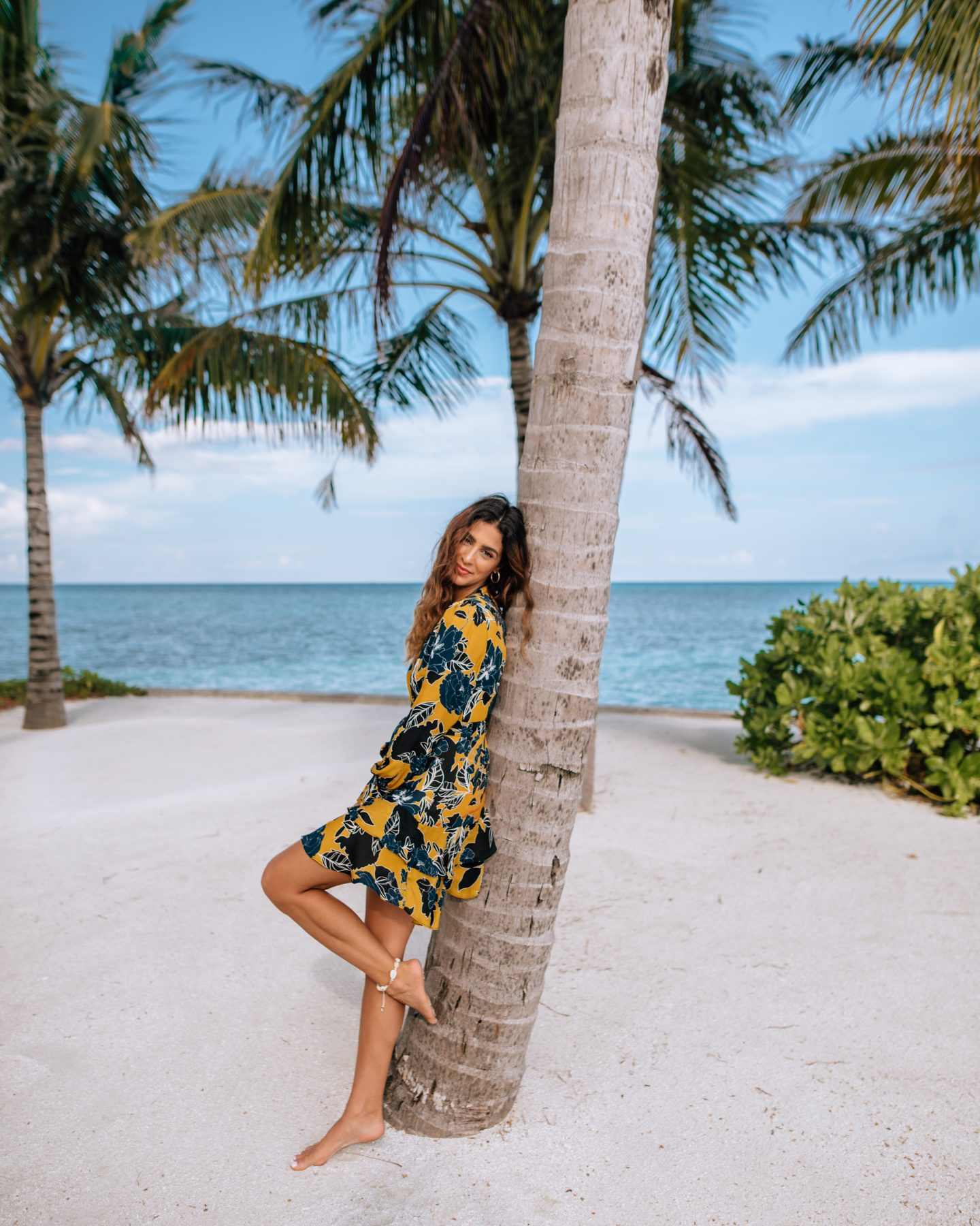 Woman leaning on palm tree on the beach at Club Med Finolhu in the Maldives