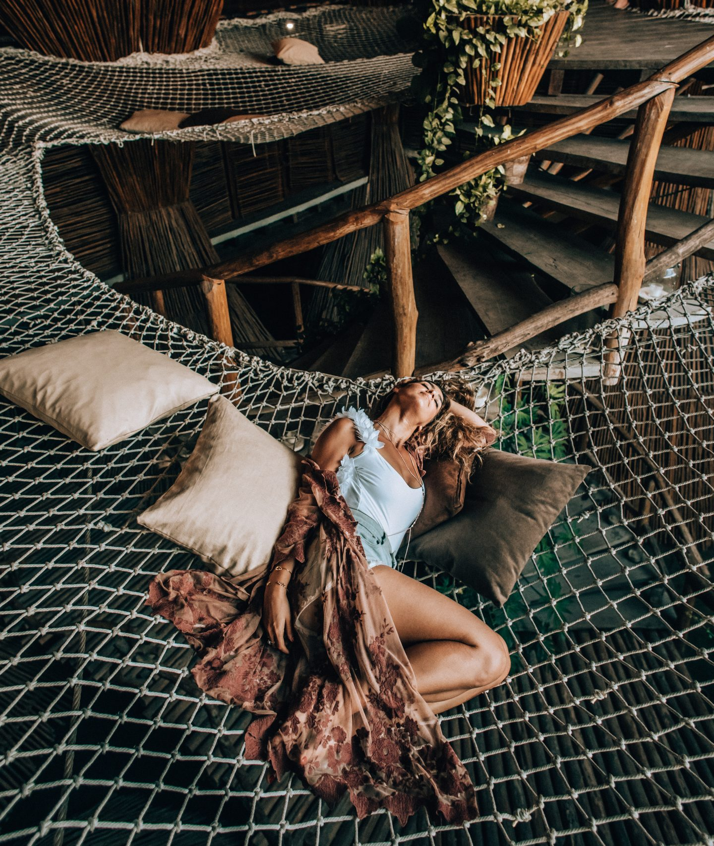 Woman lying in the hammocks of Azulik Tulum