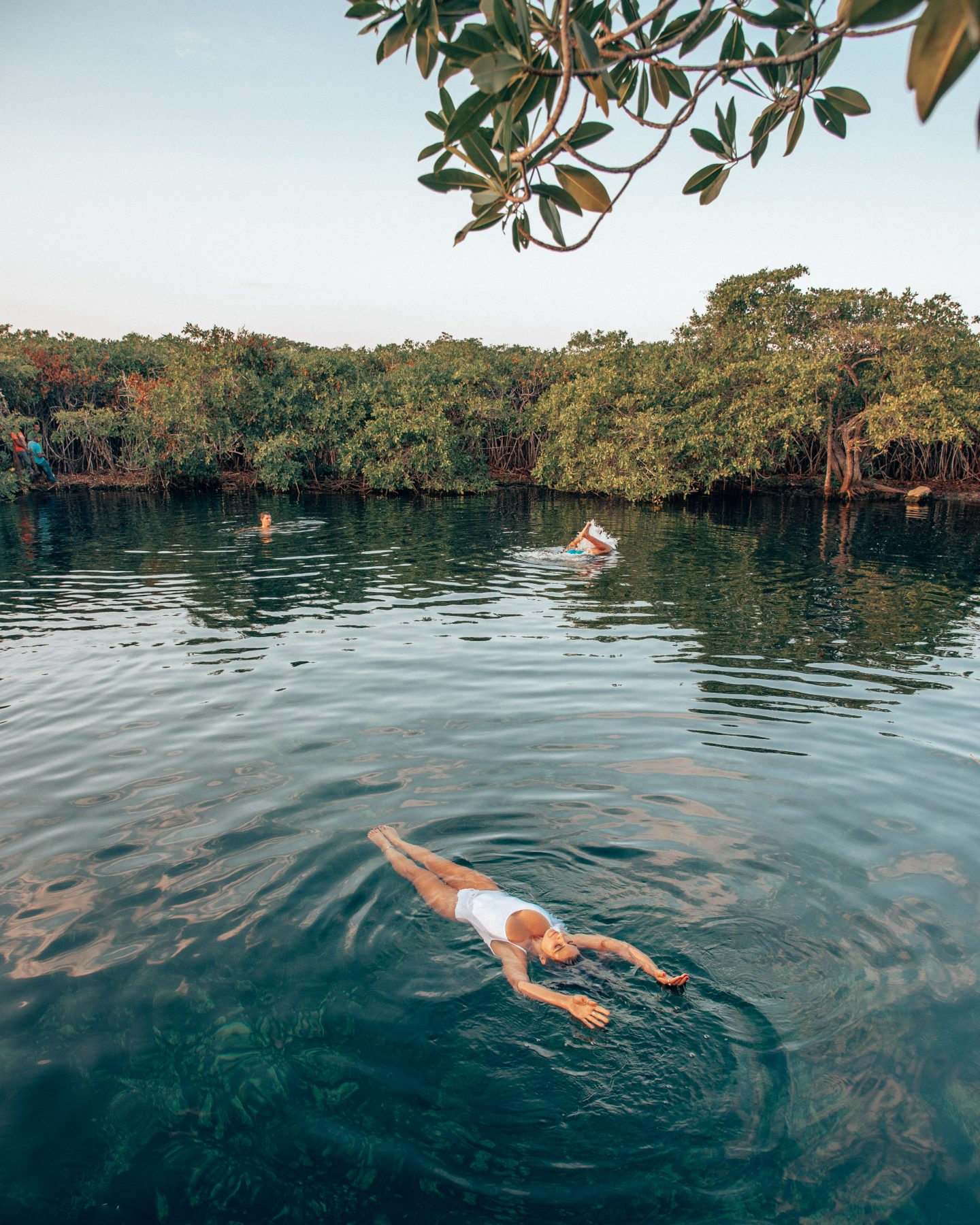 A woman floating in Cenote Kape Ha in Tulum, Mexico