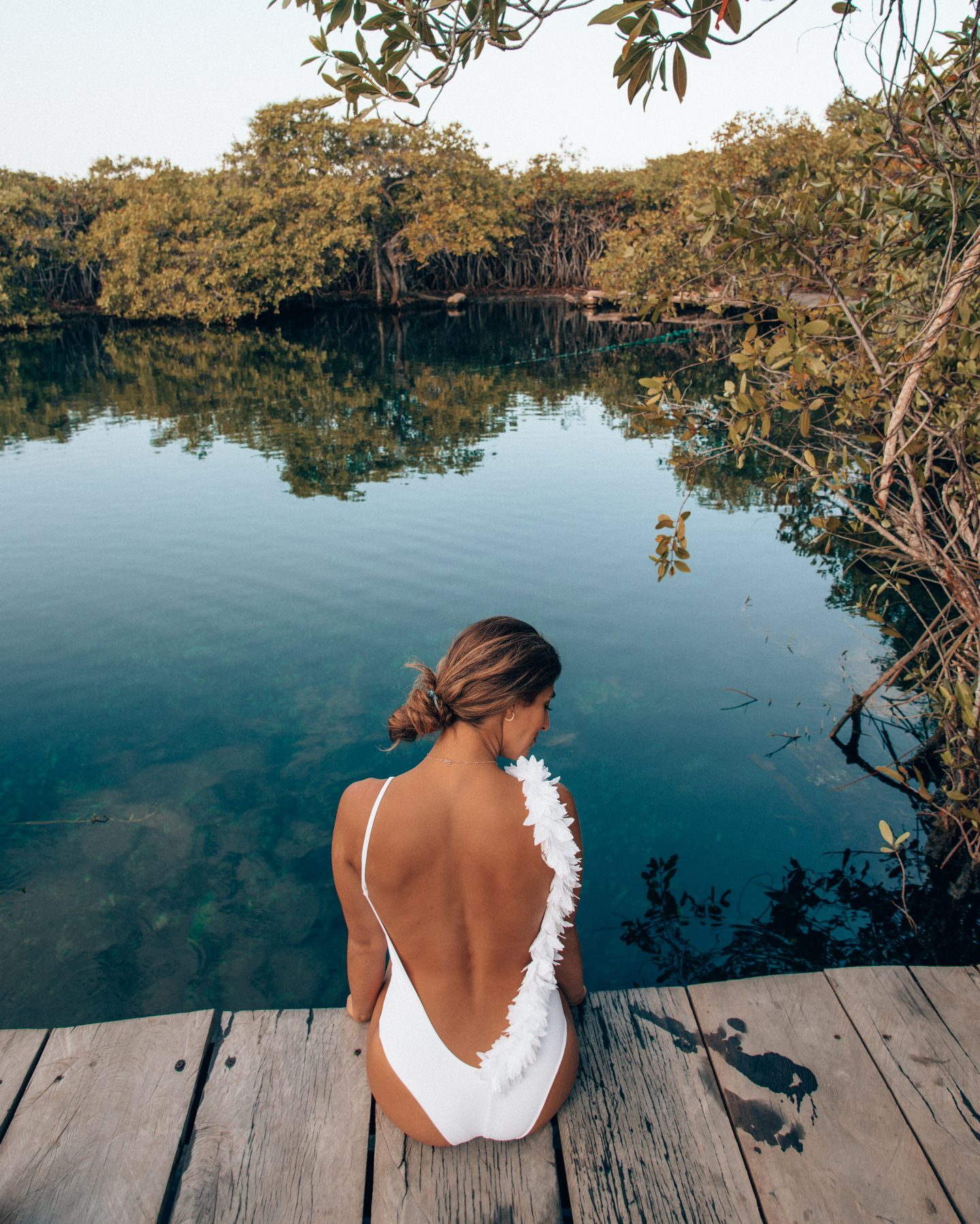 A woman sitting on the edge of a cenote in Tulum Mexico at Cenote Kape Ha