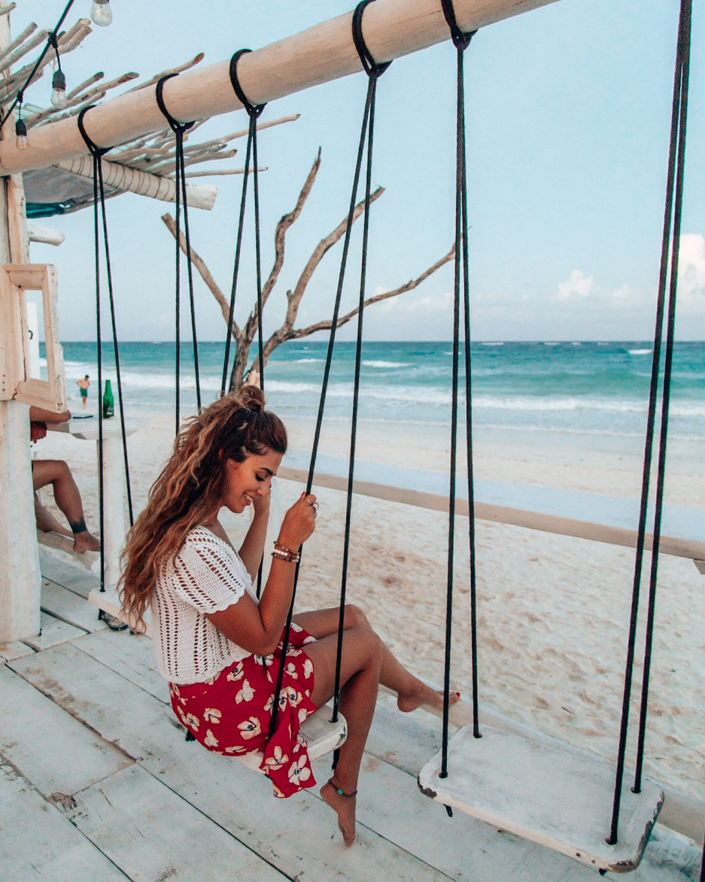 A woman on the white beach swings at Coco Tulum, a beach hotel in Tulum, Mexico