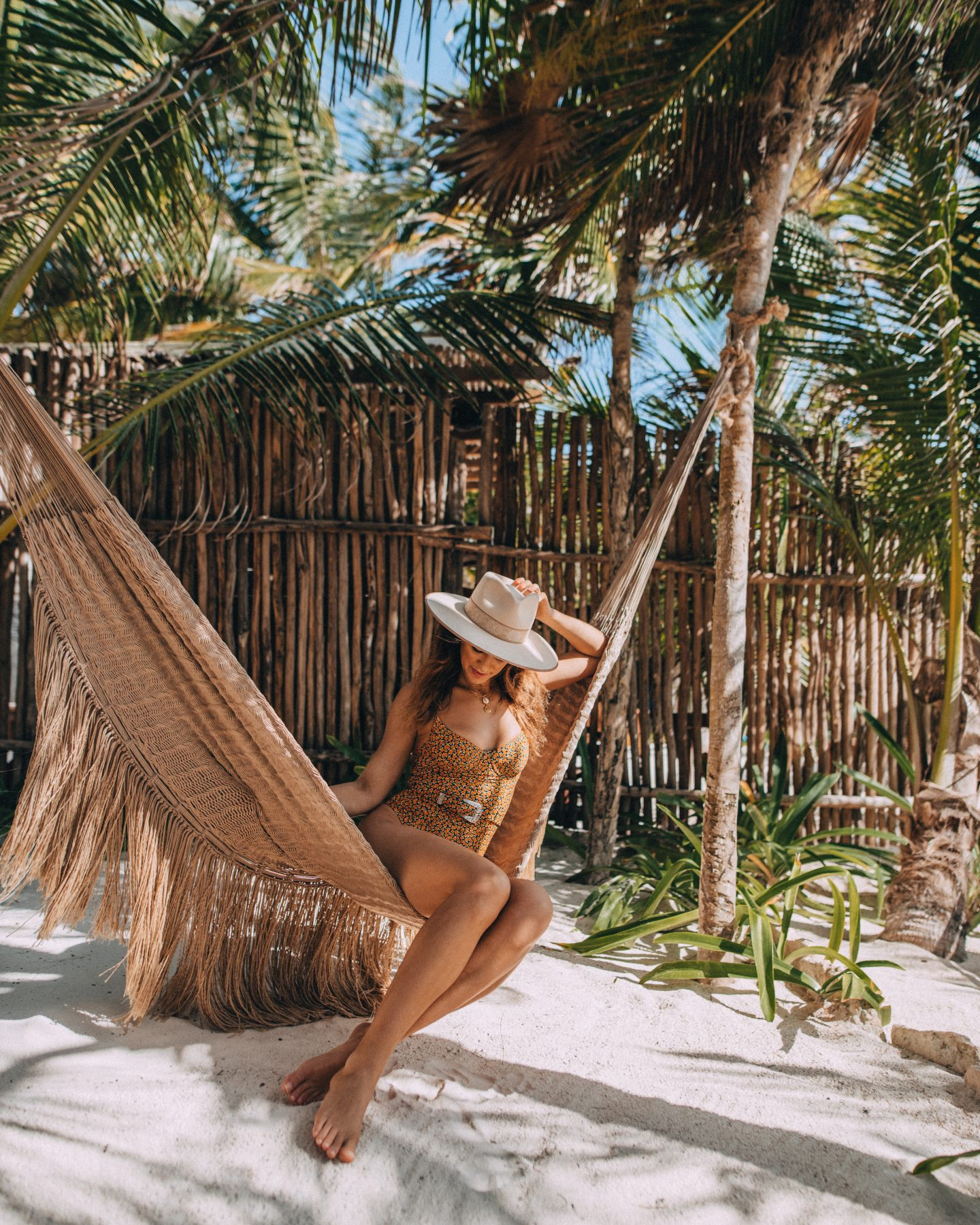 Woman in a hammock on the beach at Nest in Tulum, Mexico