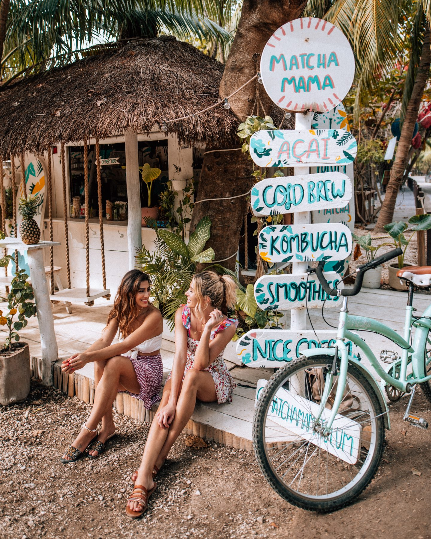 Two women sitting outside of Matcha Mama in Tulum, Mexico, one of the most Instagrammable places in Tulum.