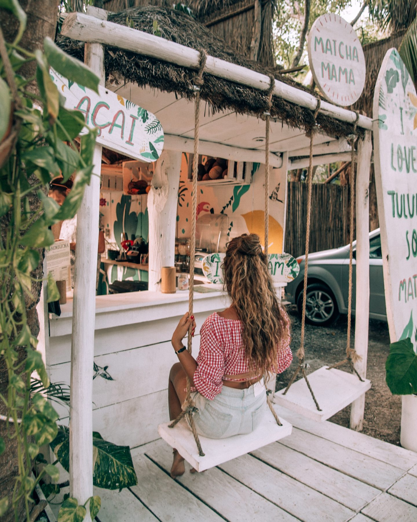 A woman on the swings at Matcha Mama, one of the famous Tulum Instagram pictures.