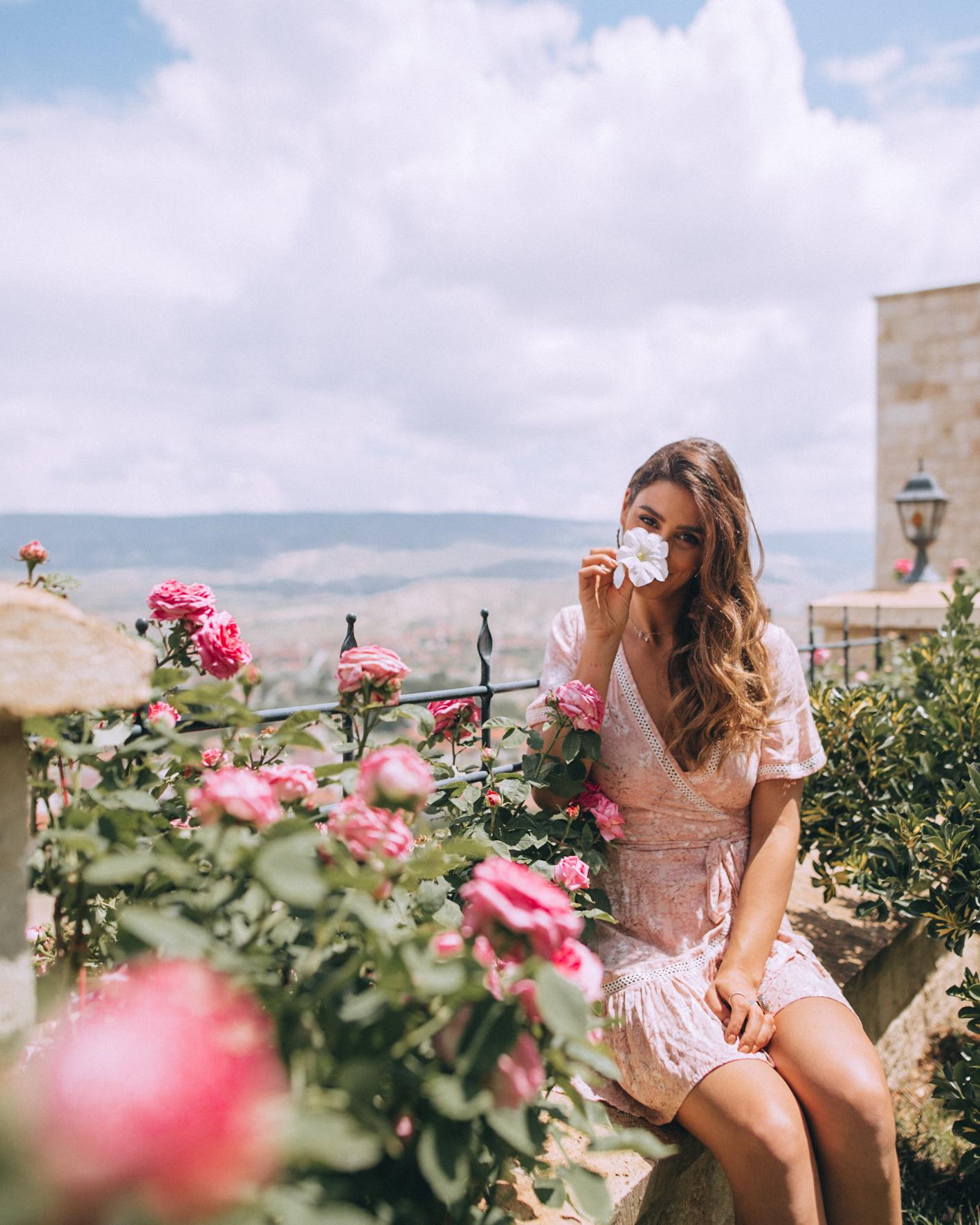 A woman smelling the roses at Kaykapi Premium Cave hotel in Cappadocia
