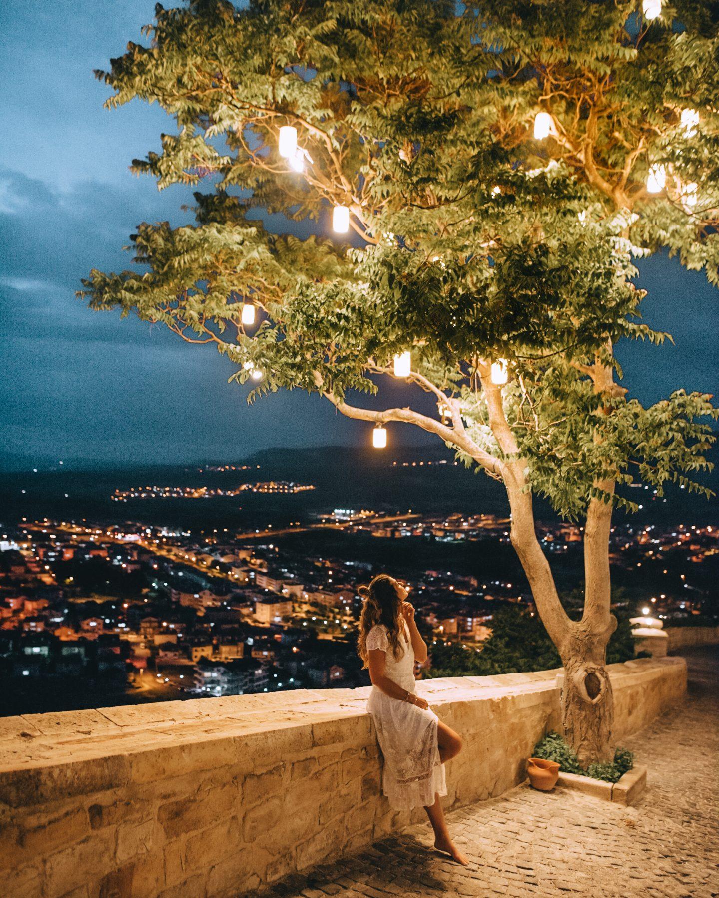 A woman under a lantern lit tree at Kaykapi Premium Caves in Cappadocia