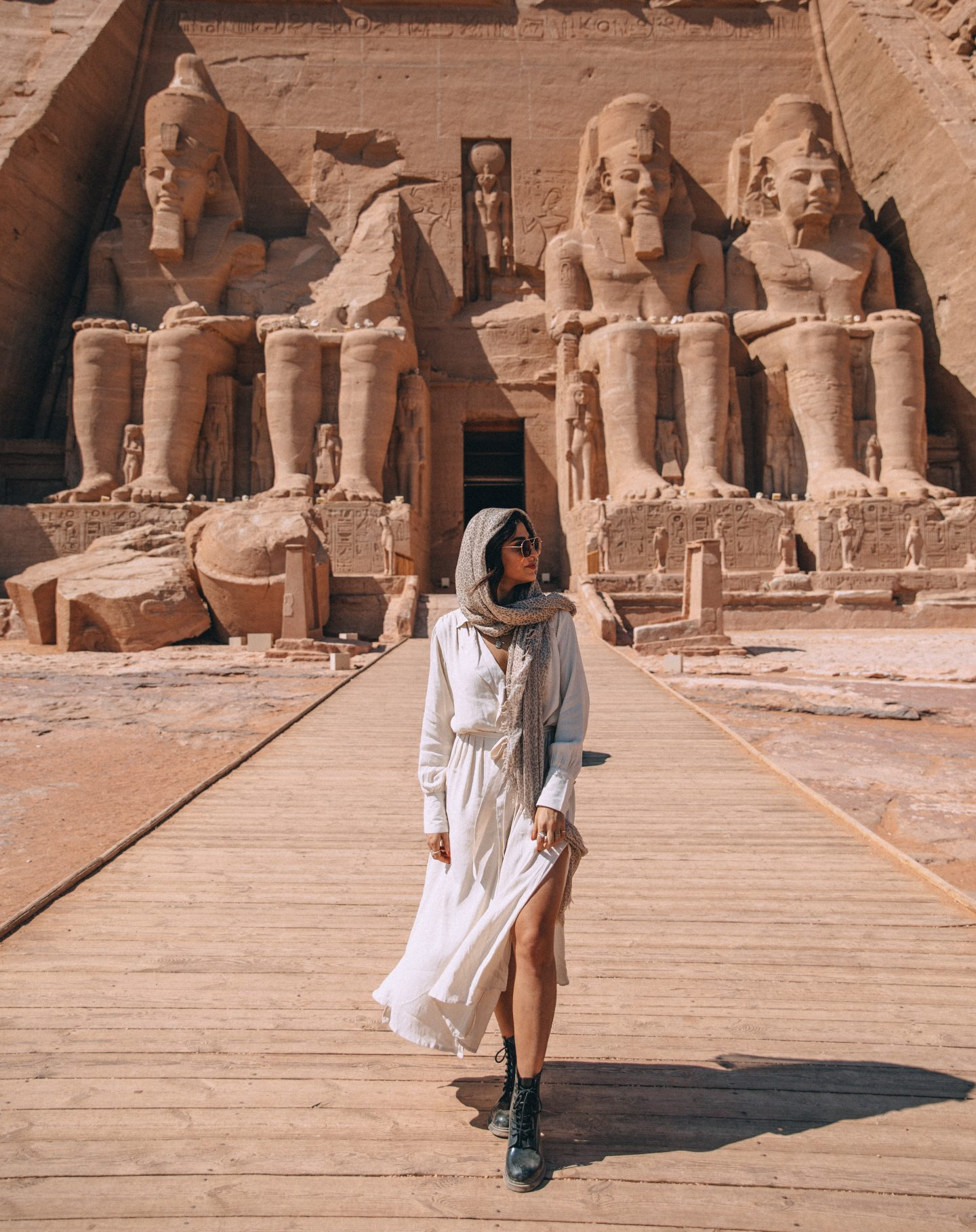 A woman posing in front of the temple at Abu Simbel in Egypt.