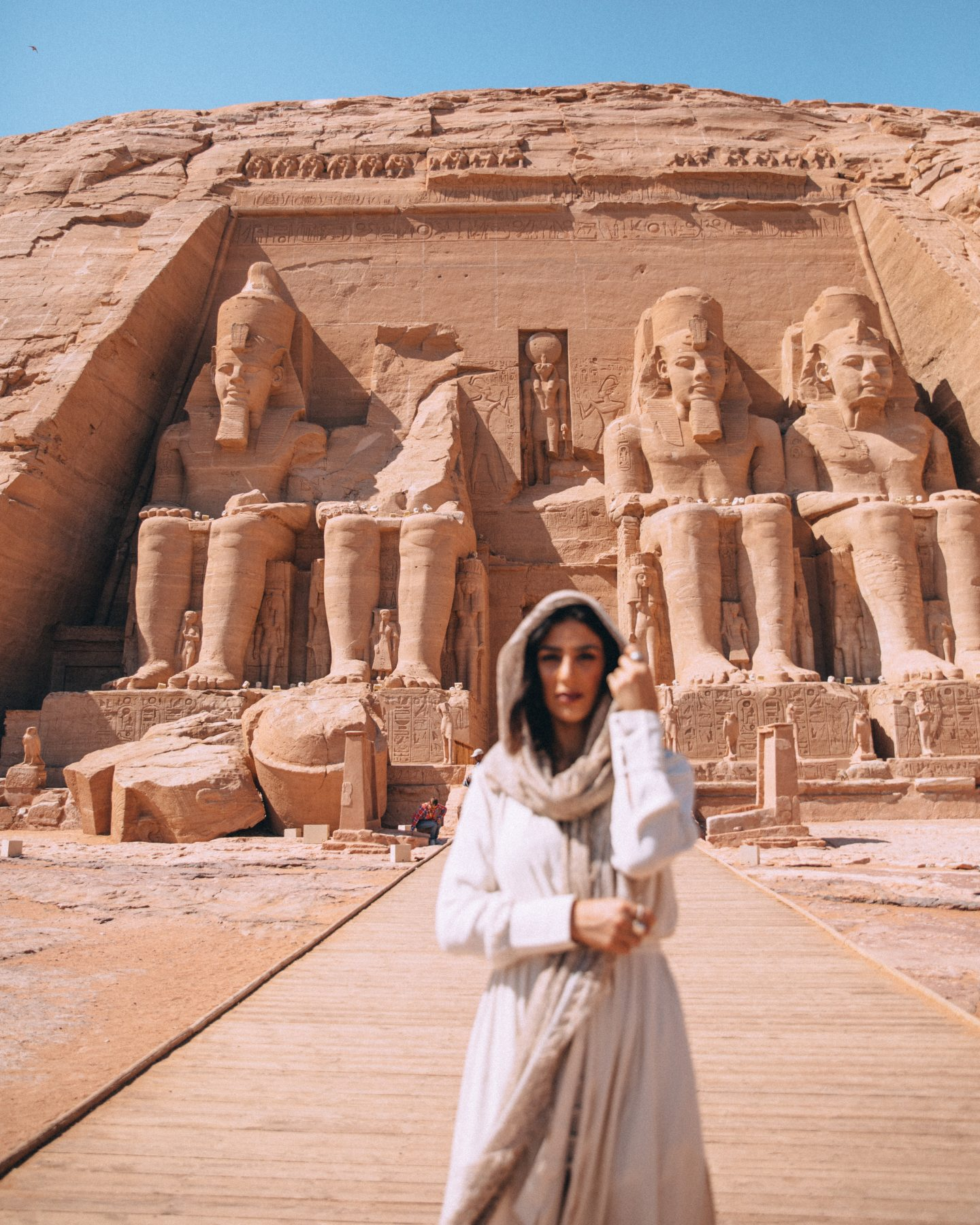 A woman walking away from the Temple of Ramesses in Abu Simbel, Egypt.