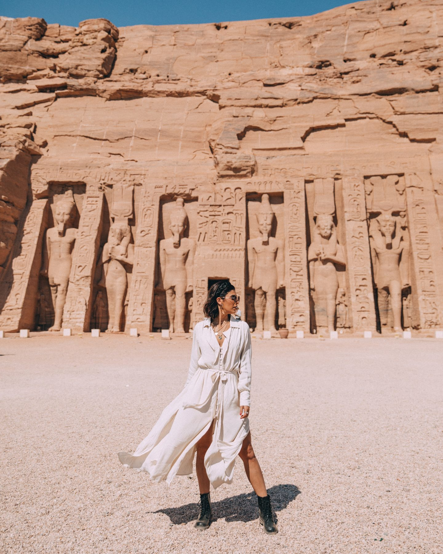 A woman poses in front of the Temple of Queen Nefertari in Abu Simbel, Egypt