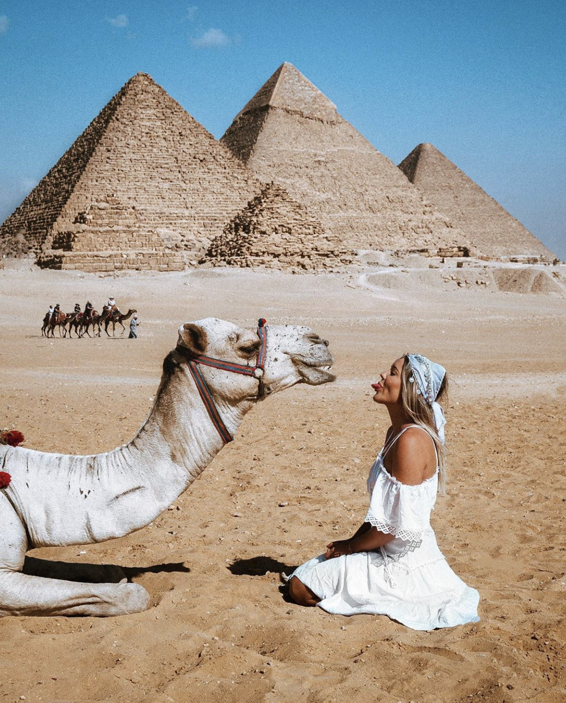 A woman sticking her tongue out at a camel in front of the Great Pyramids in Cairo, Egypt.