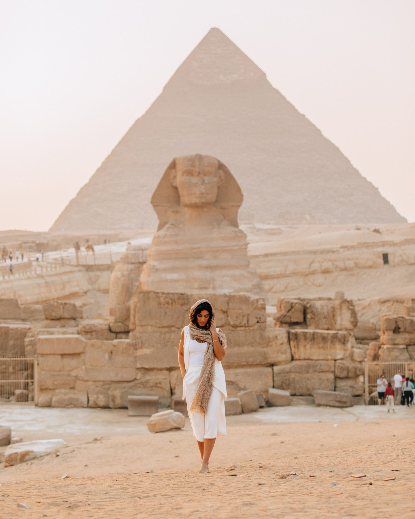 A woman walking away from the Sphinx in front of the Great Pyramid in Cairo, Egypt
