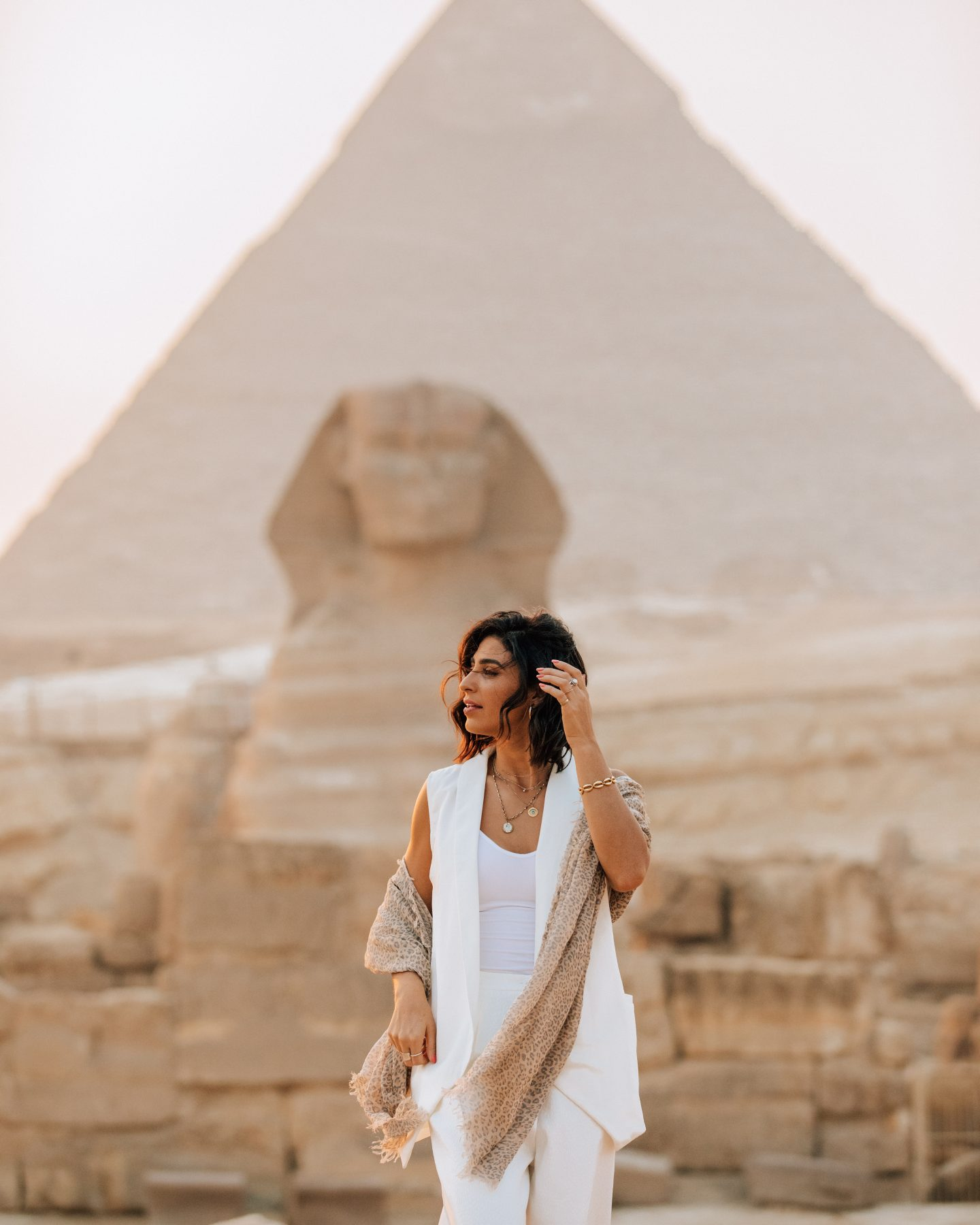 A woman in front of the Great Sphinx and Great Pyramids of Giza in Egypt