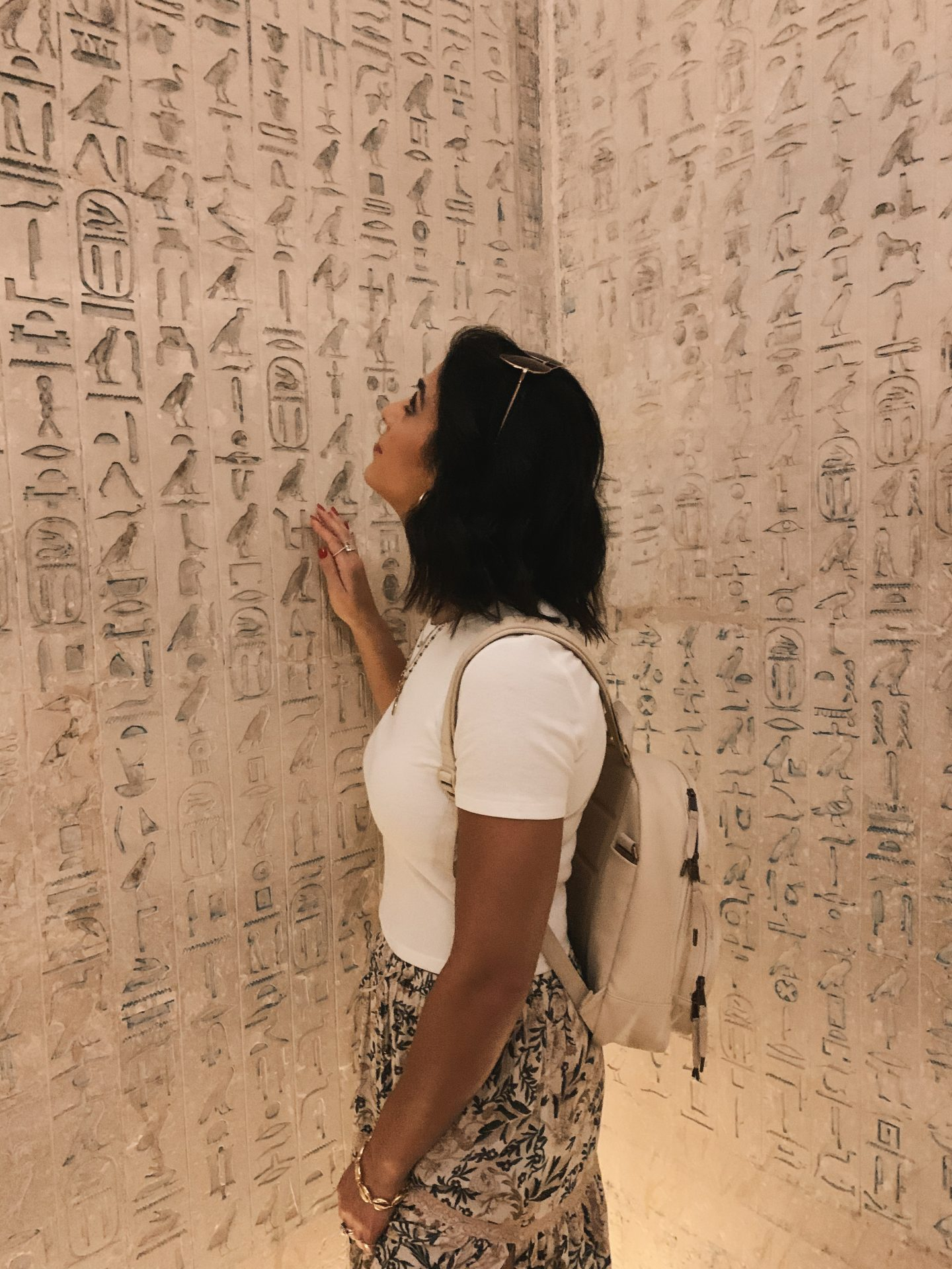 A woman looking at Egyptian hieroglyphics inside a pyramid in Egypt at Saqqara.
