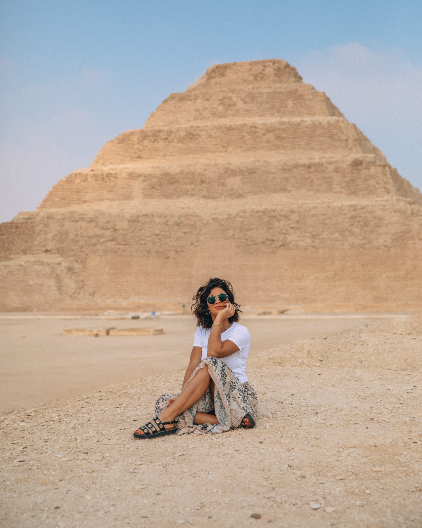 A woman sitting in front of the step pyramid at Saqqara
