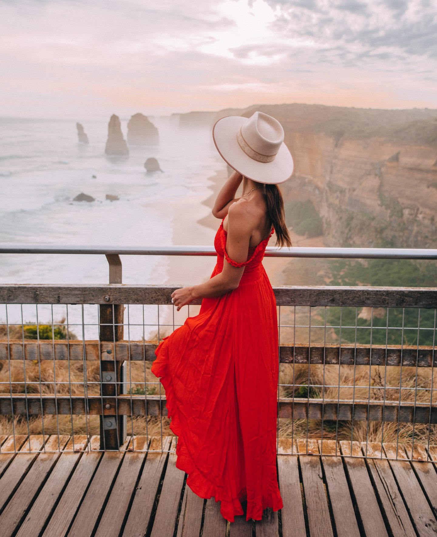 A woman in a red dress looking out at the Twelve Apostles in Australia on Great Ocean Road