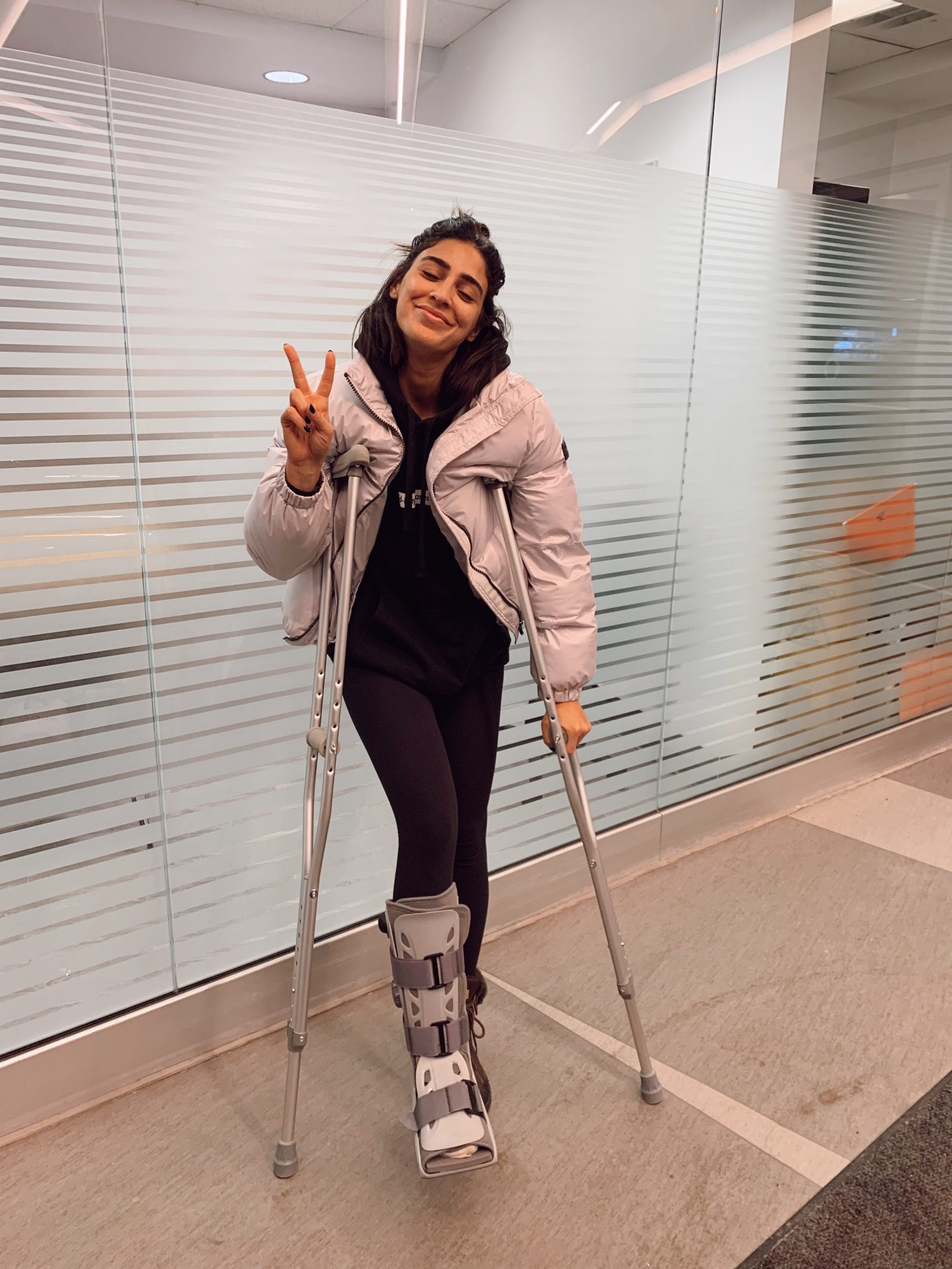 A woman poses with a broken ankle wearing a walking boot and using crutches