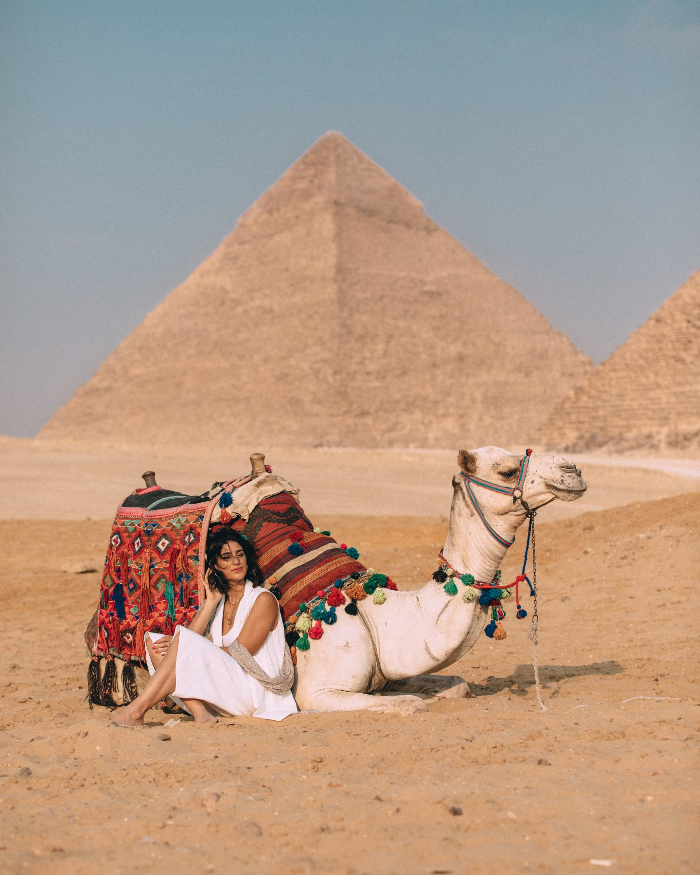 A woman sitting by a camel in front of the Great Pyramids of Giza in Cairo, Egypt