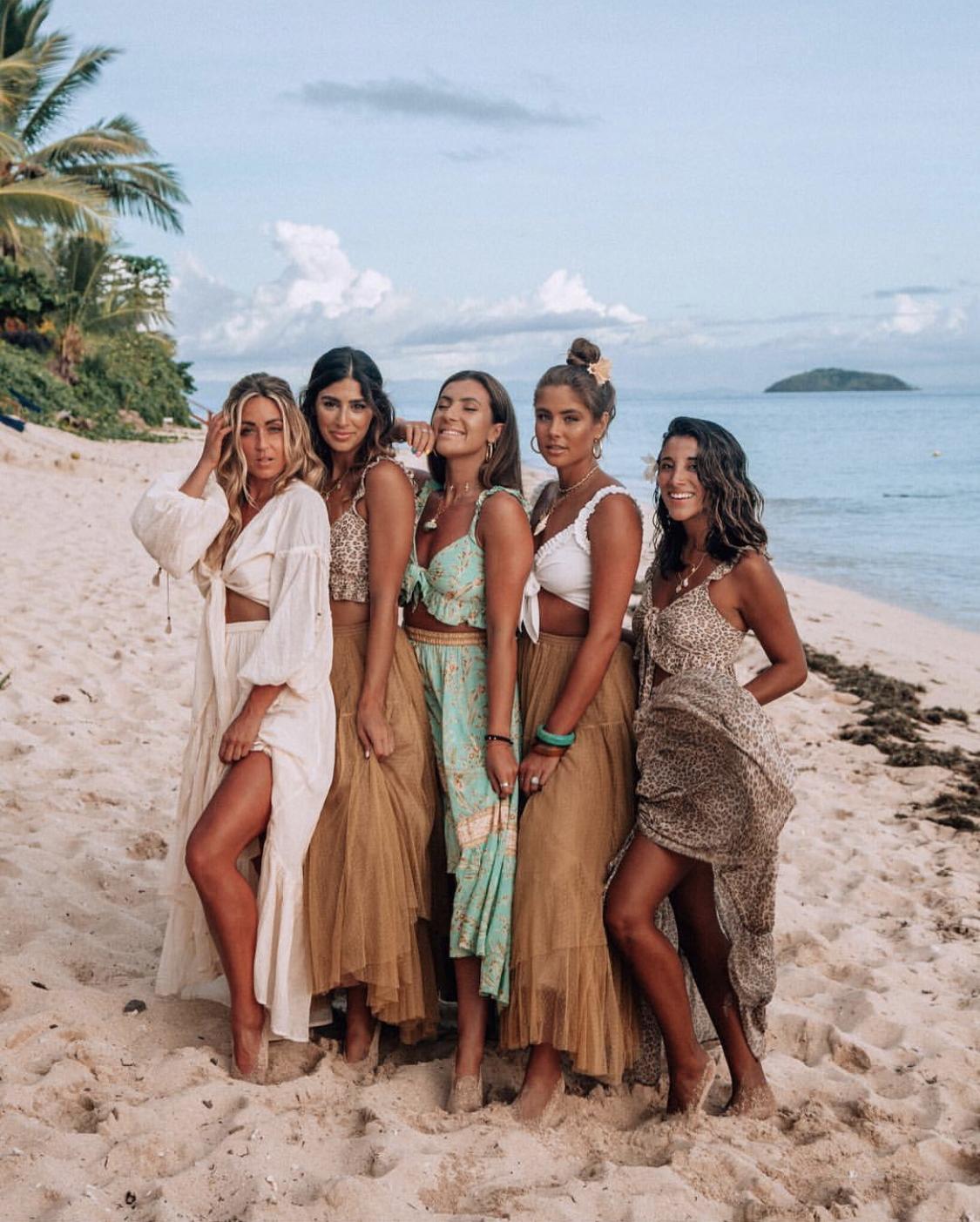 A group of travel influencers pose on the beach in Fiji working on a brand campaign