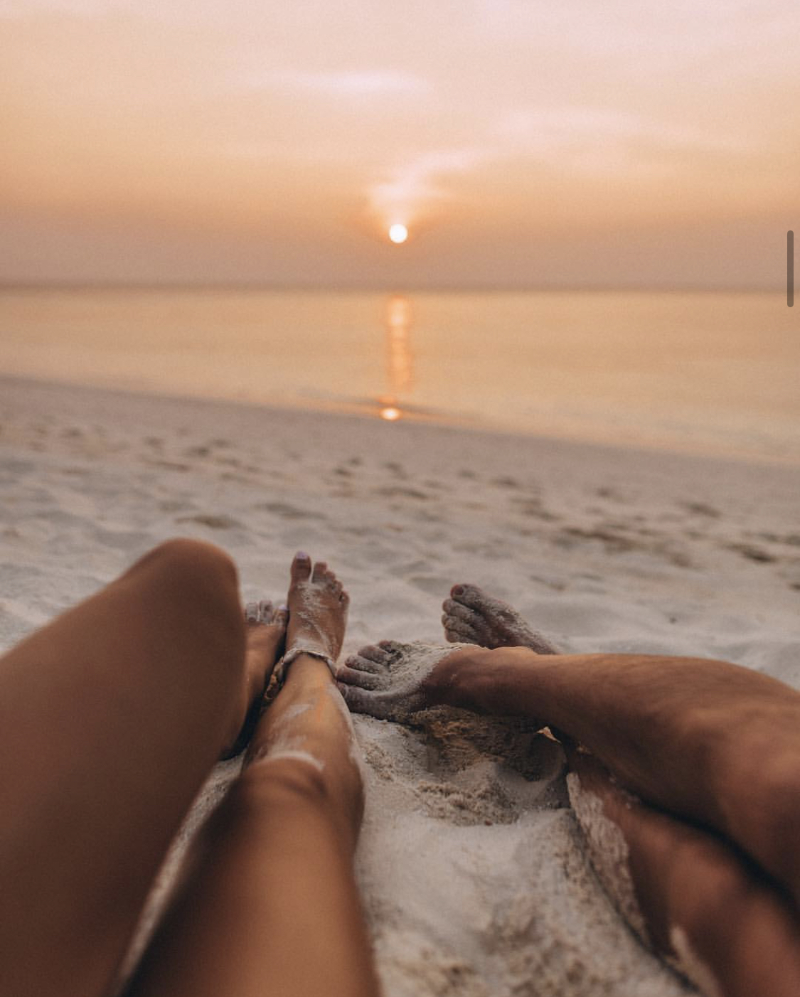 A couple poses on the beach at sunset in the Maldives