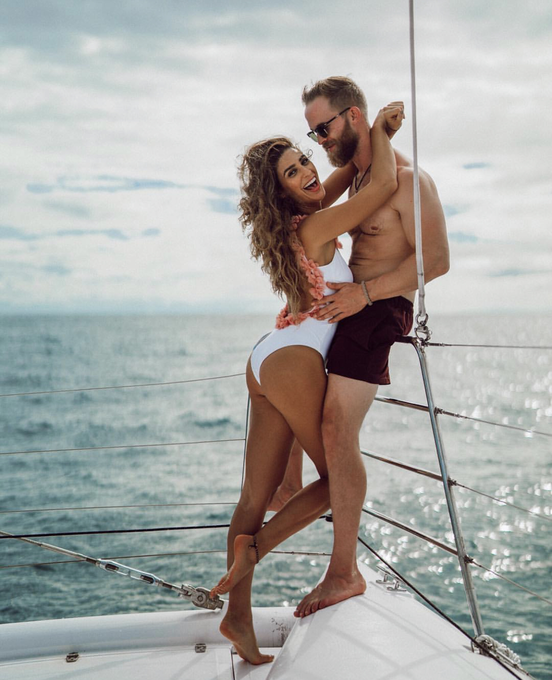 A couple poses on a boat in Jamaica