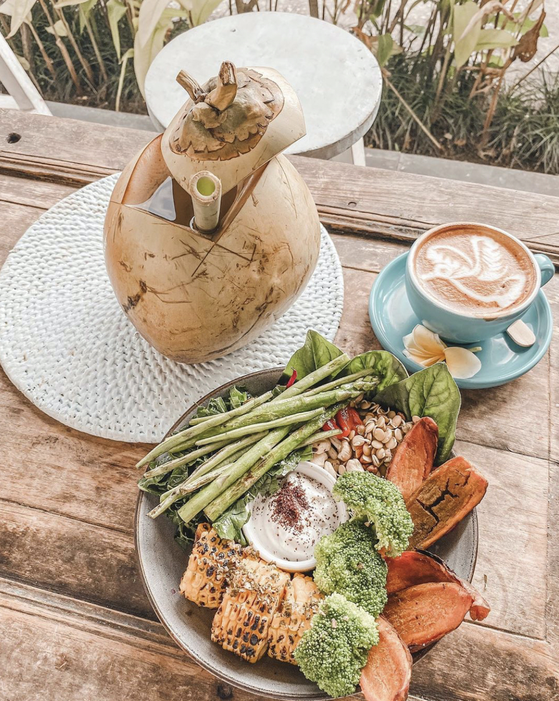 A coconut, a latte, and a plate of food at Shady Shack in Bali