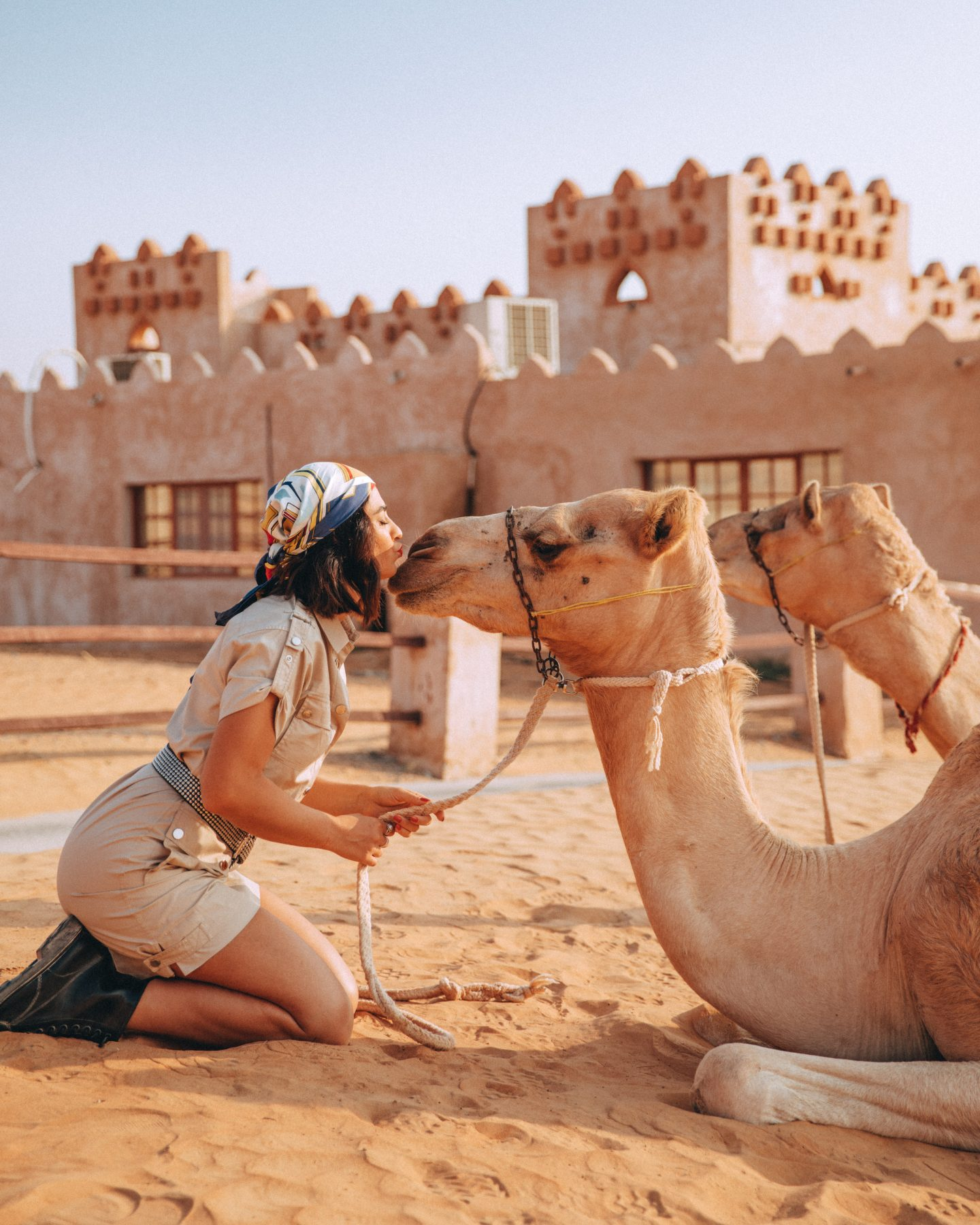 A woman kisses a camel at 1000 Nights Camp in the desert in Oman