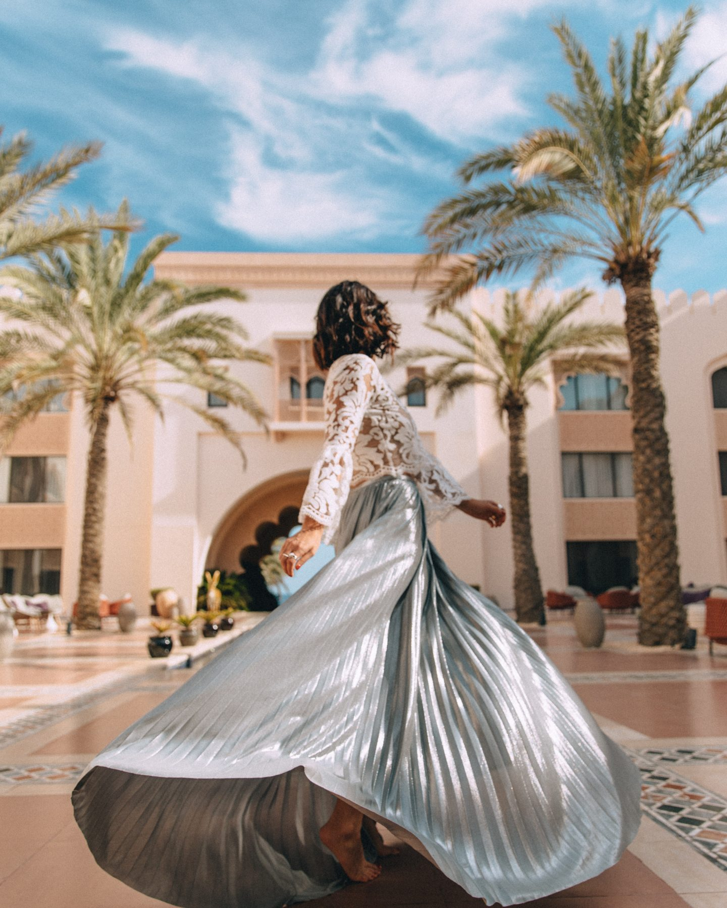 A woman twirling at Shangri-La Al Husn in Muscat, Oman