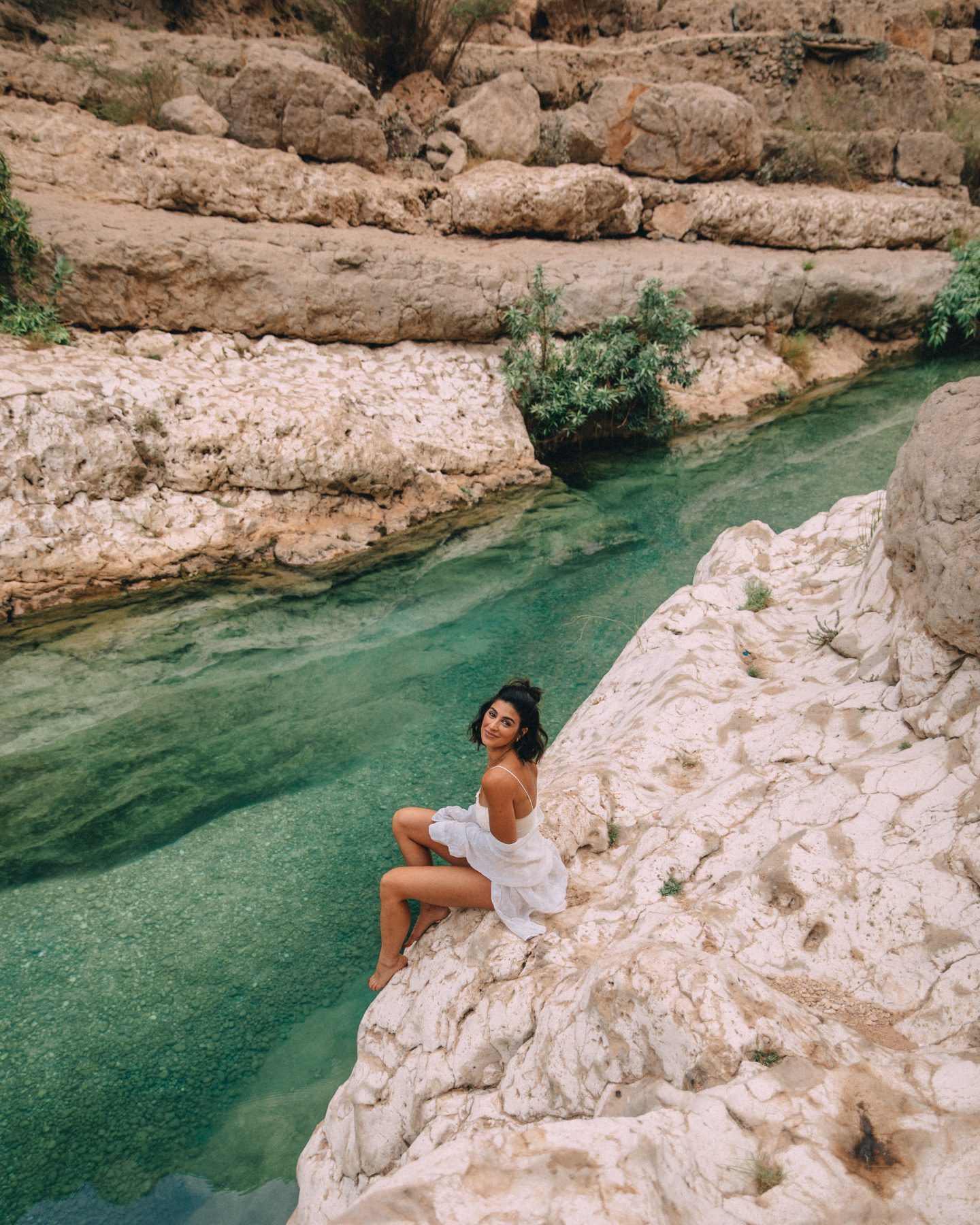A woman sitting on the rocks in Wadi Shab, Oman
