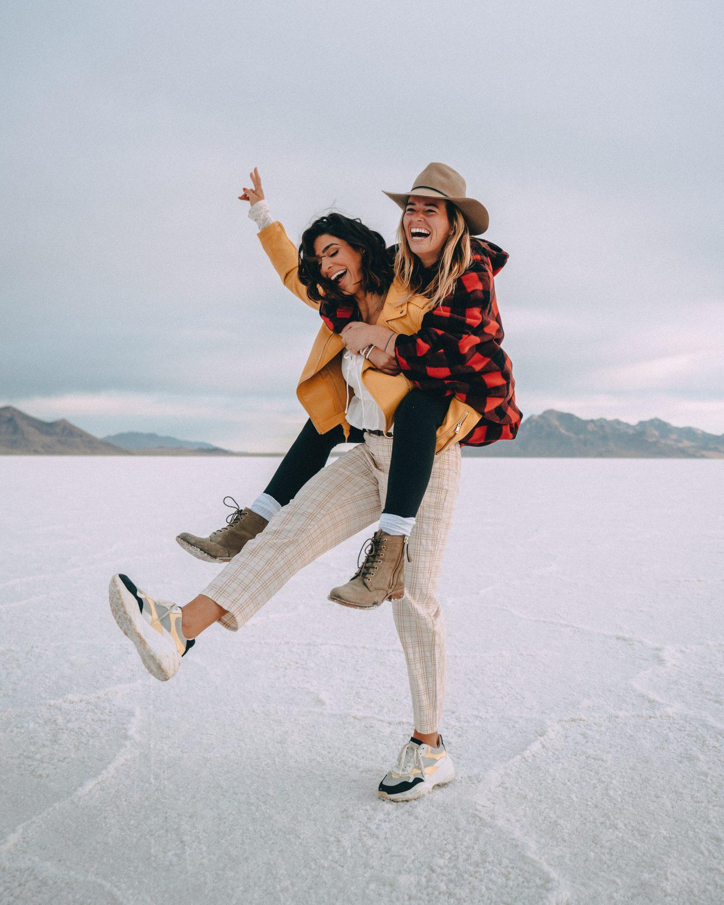 Women posting for Instagram at Bonneville Salt Flats on a road trip in Utah