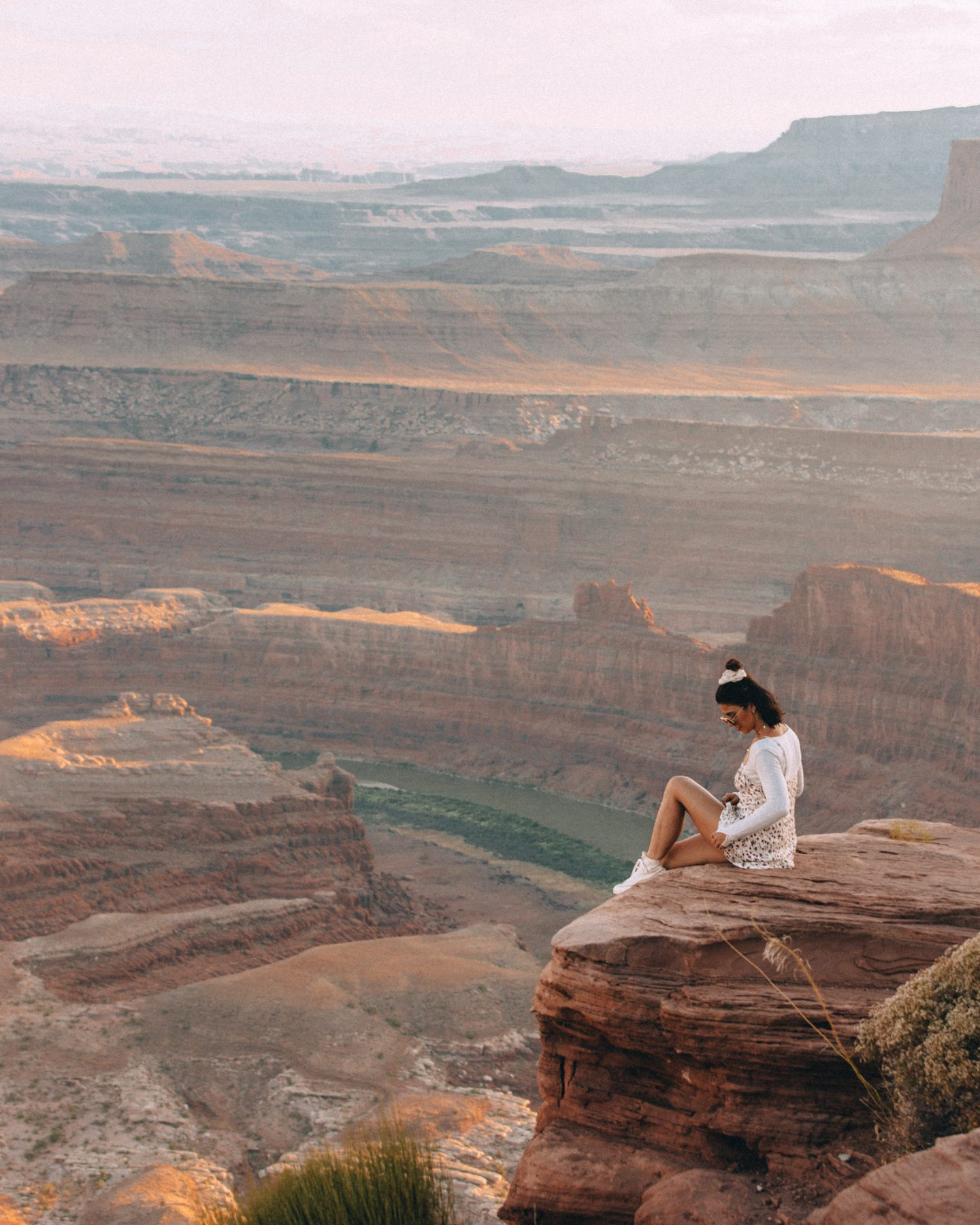Woman sitting on the edge of the canyon at Dead Horse Point in Moab, Utah