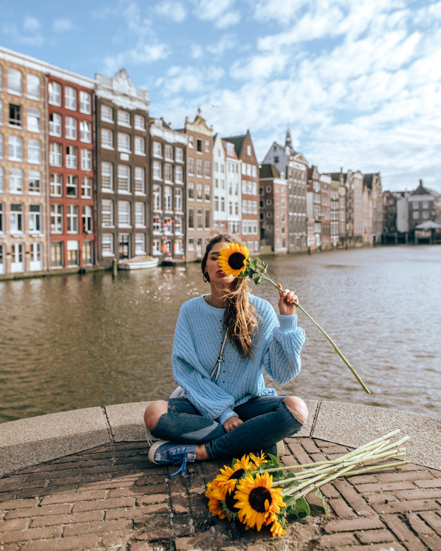 Using sunflowers as a prop to help with posing for Instagram pictures in Amsterdam
