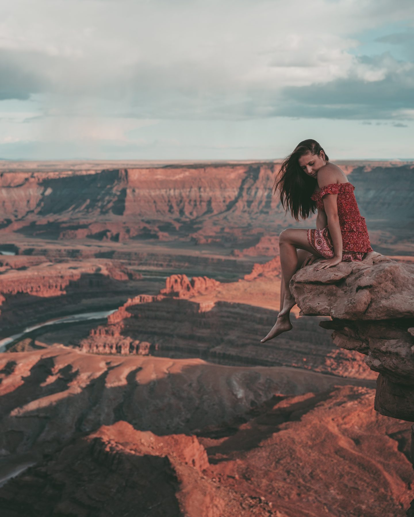 Woman sitting with feet dangling over the edge of Dead Horse Point in Utah