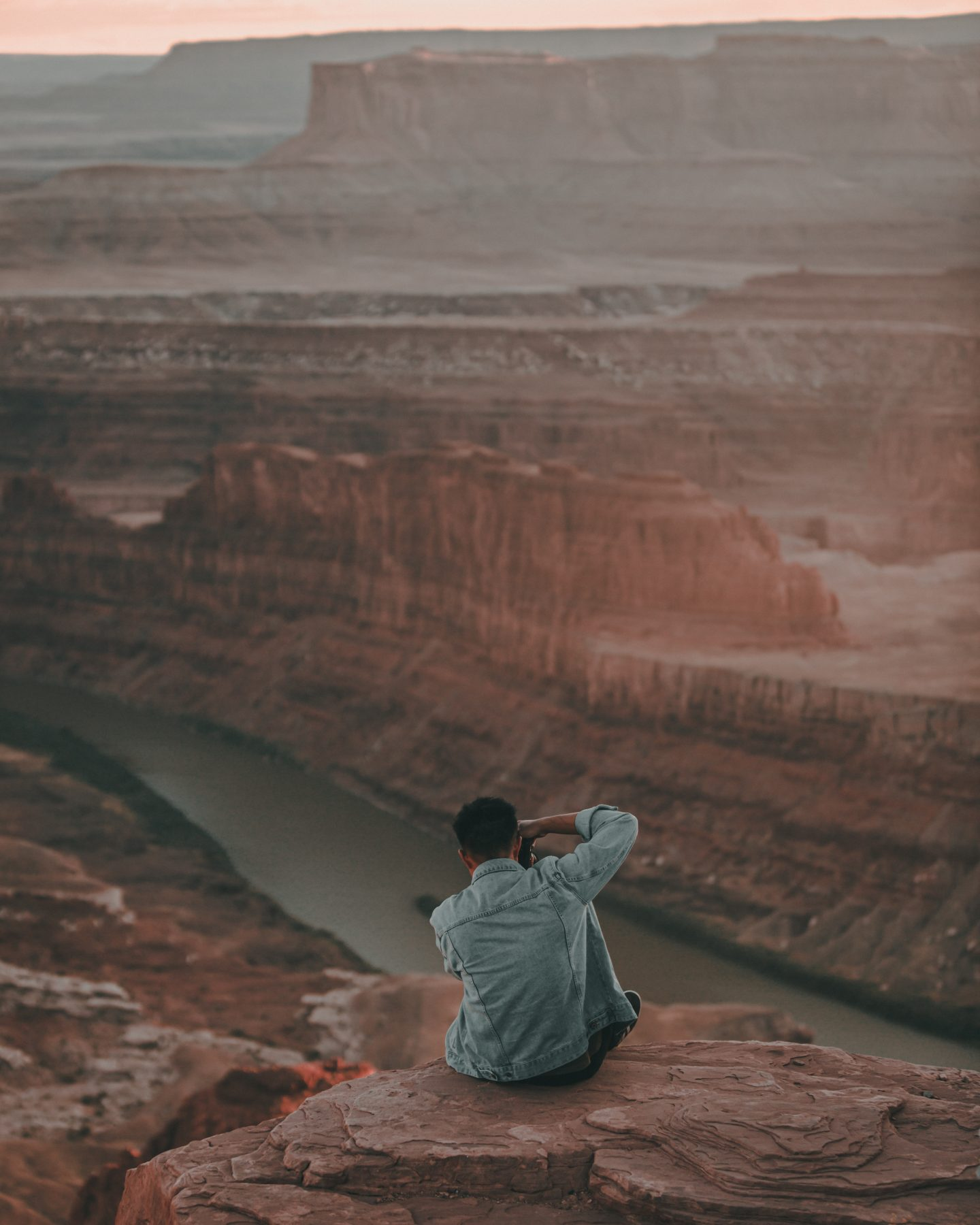 Photographer sits on the edge of Dead Horse Point