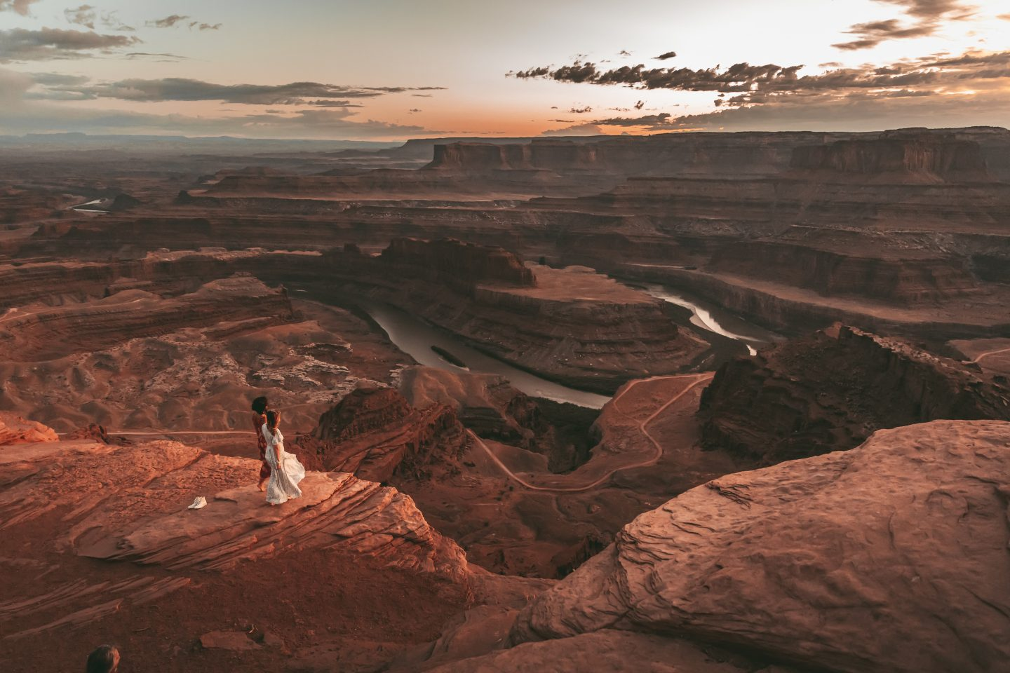 Two women look out over the sunset at Dead Horse Point in Utah