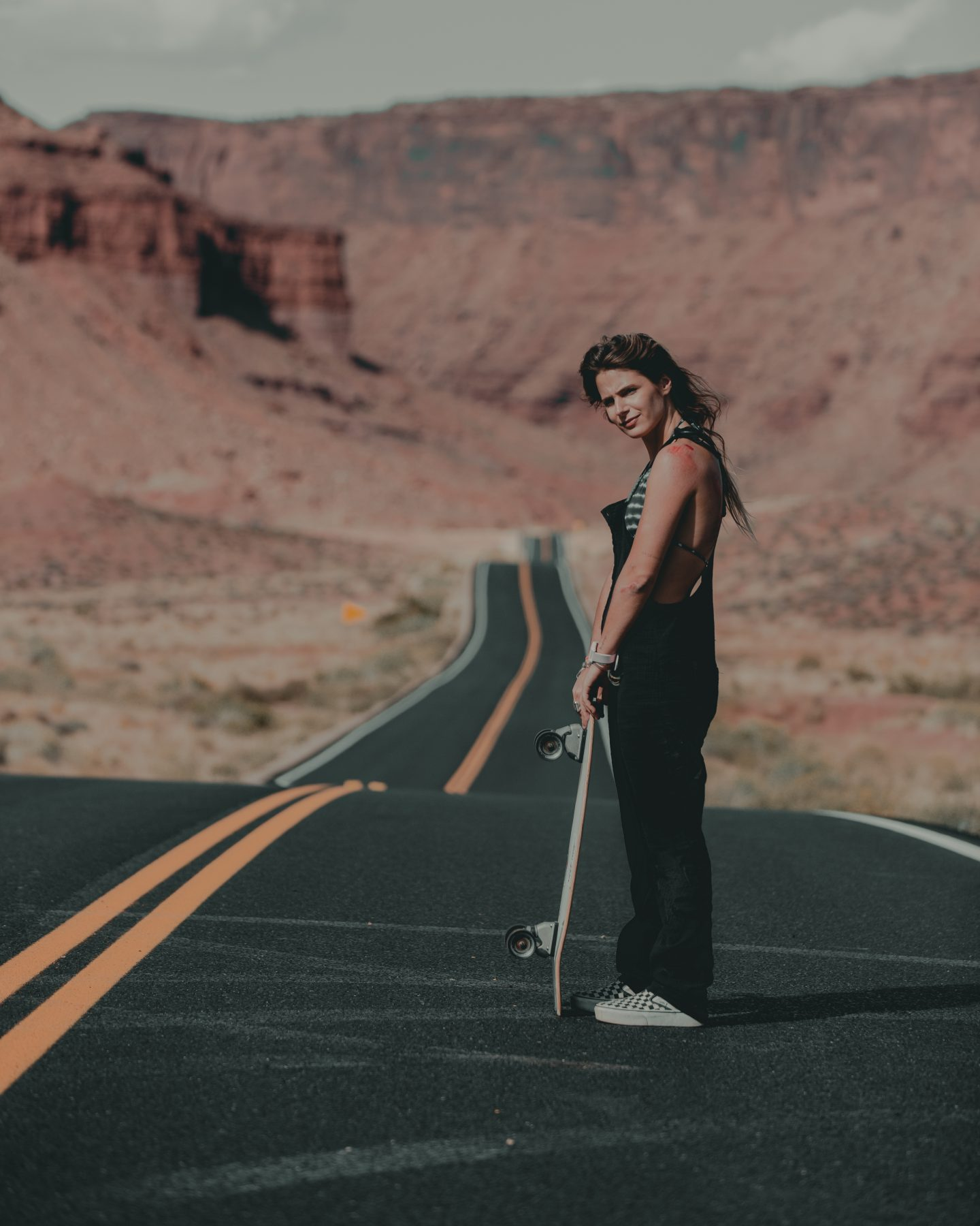 Woman with a skateboard in the middle of the road in Utah