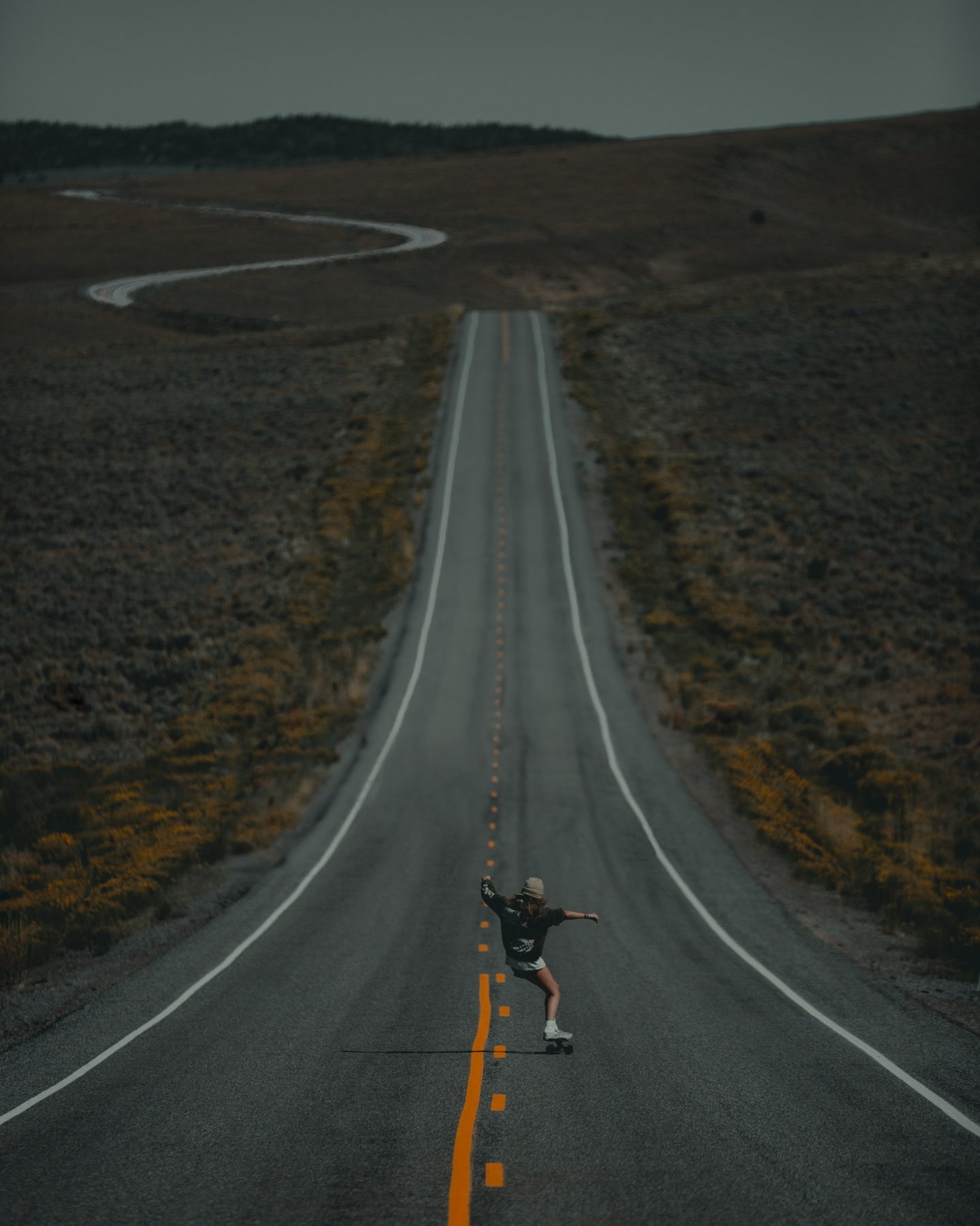 Woman skateboards down the road in Utah