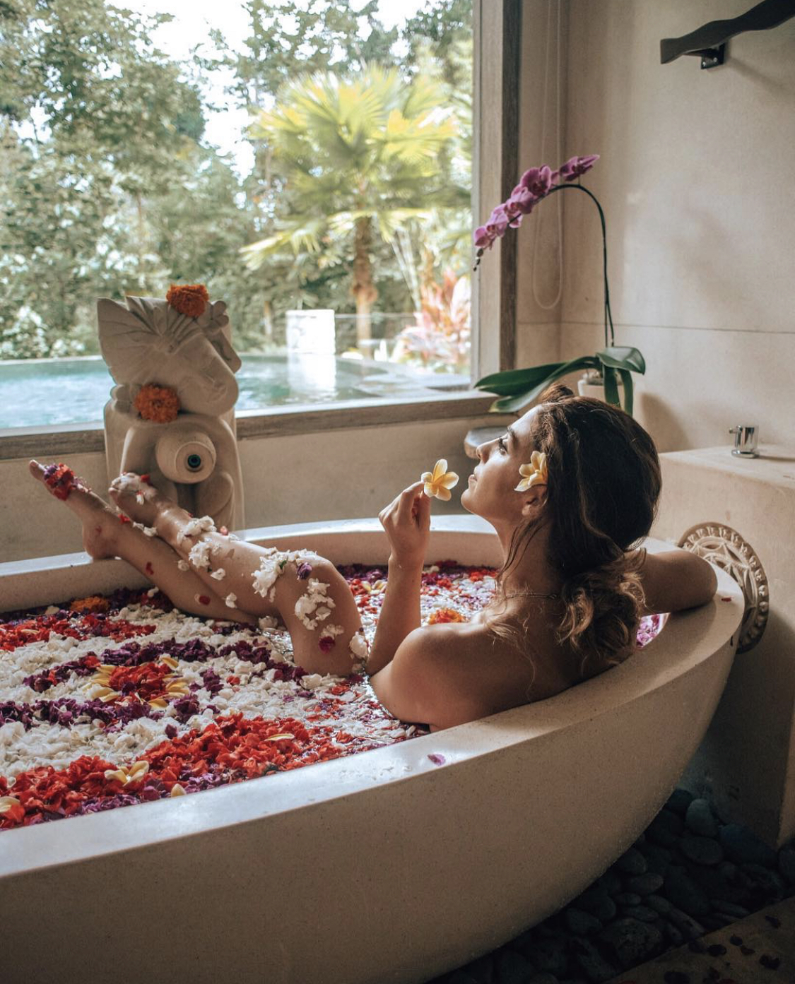 Woman taking a flower bath at The Udaya in Ubud, Bali