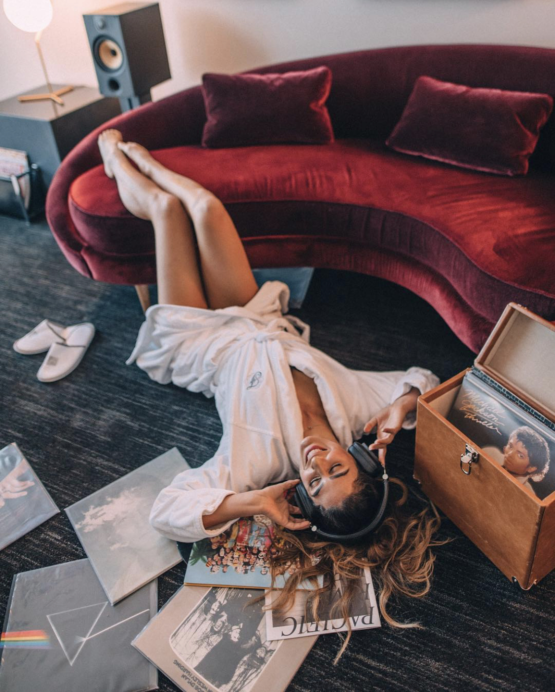 Woman in a robe laying on the ground listening to records at a hotel